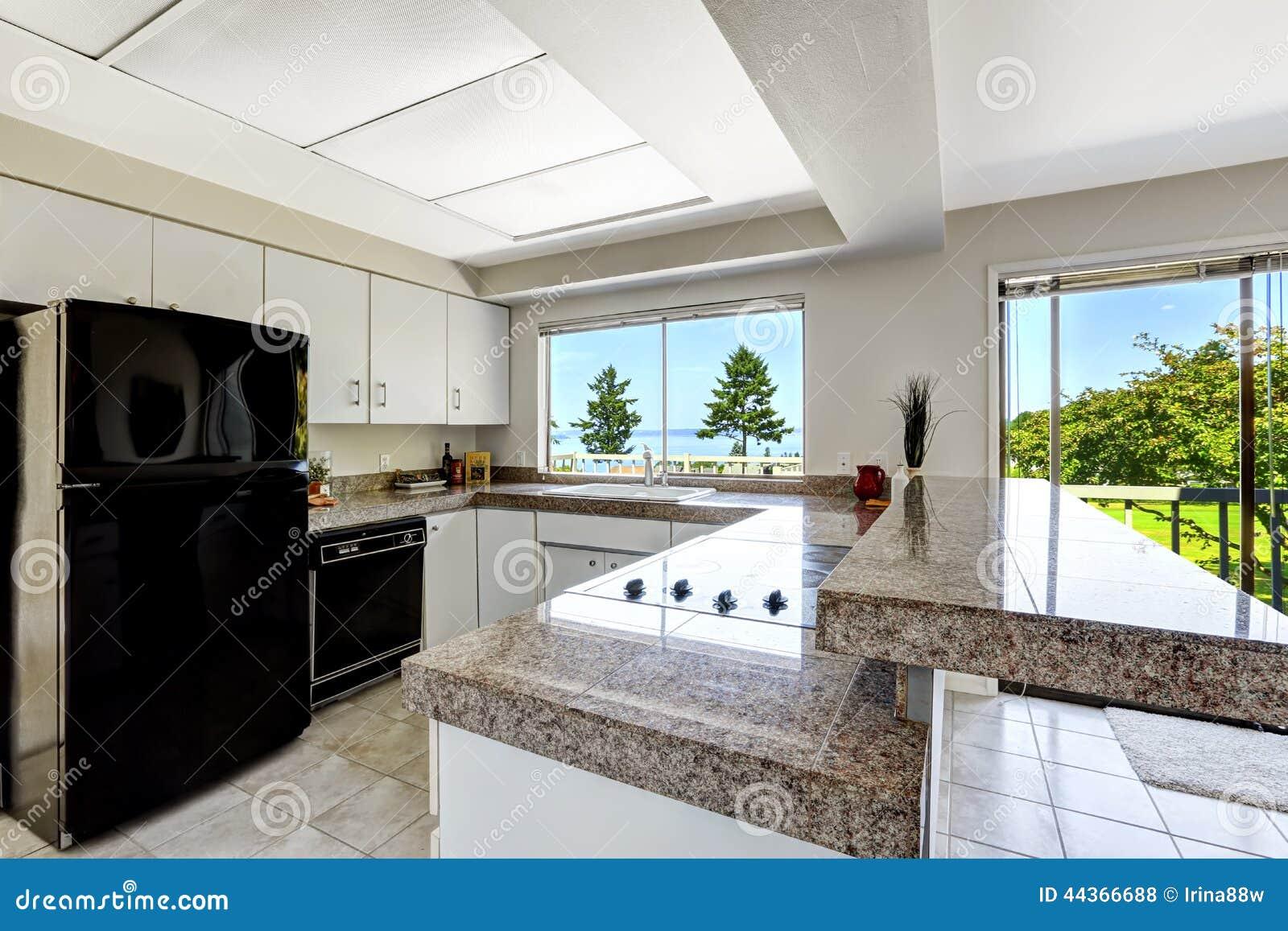 Witte keukenruimte met zwarte toestellen en granietbovenkanten ...