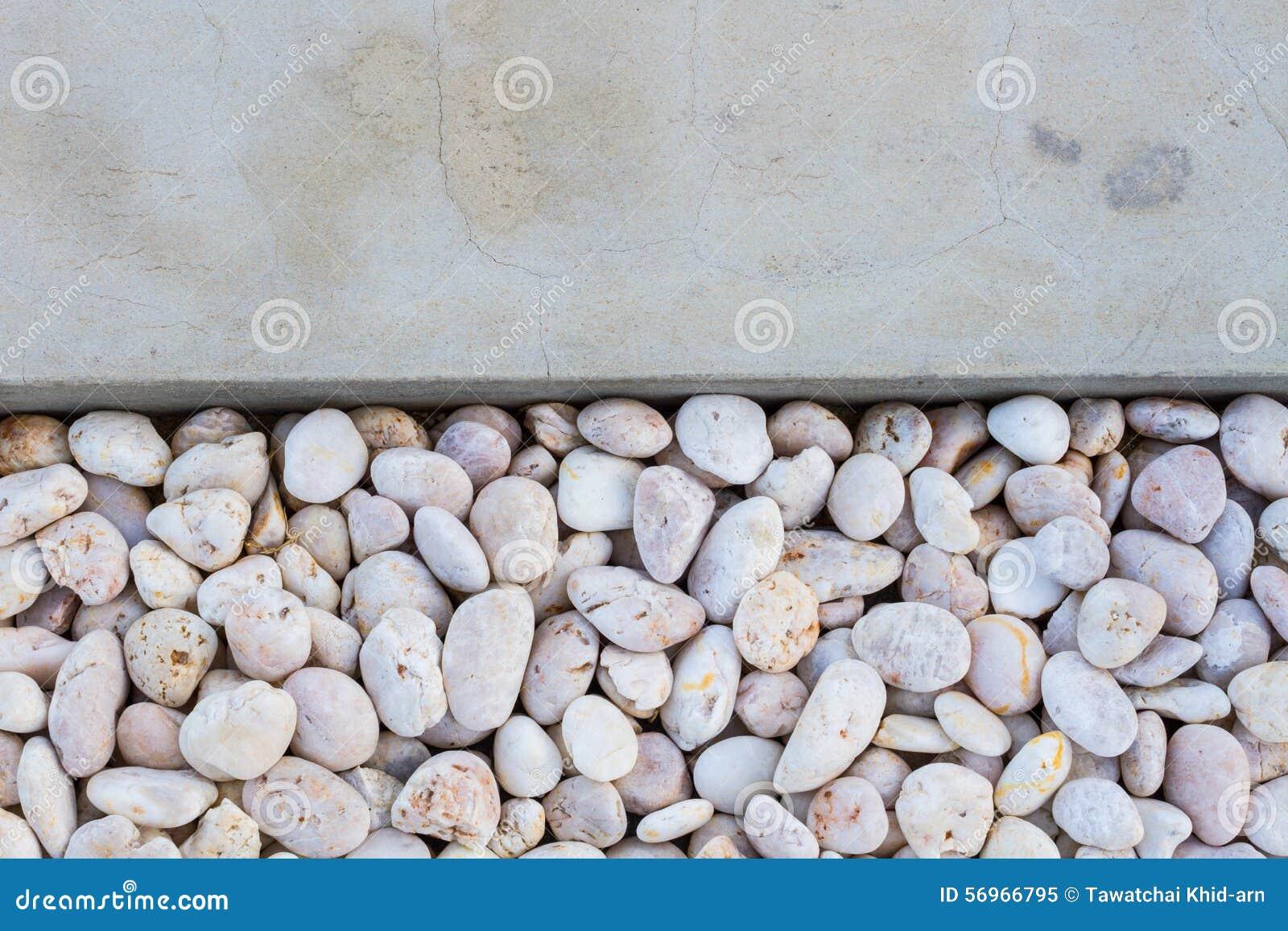 Witte kiezelsteenstenen met grijze concrete grond stock afbeelding