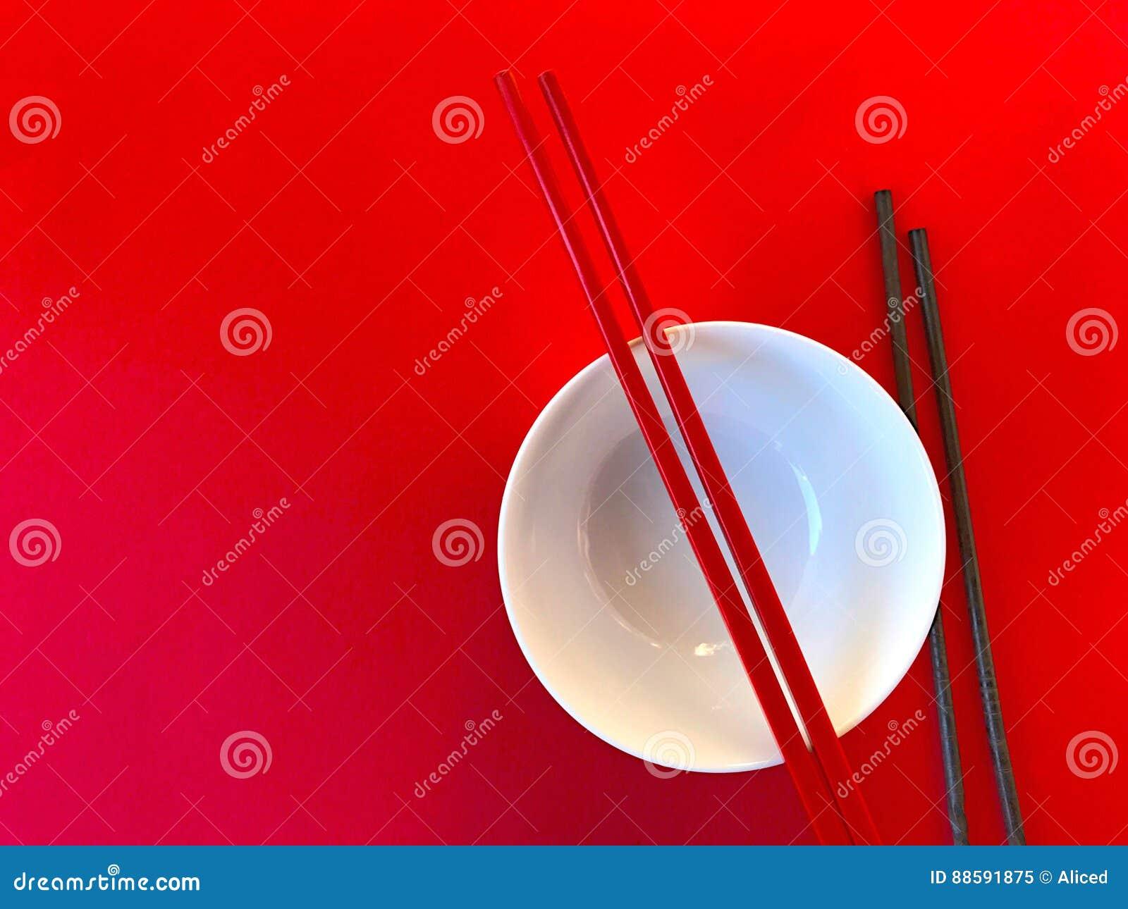 Witte kom met eetstokjes op rood