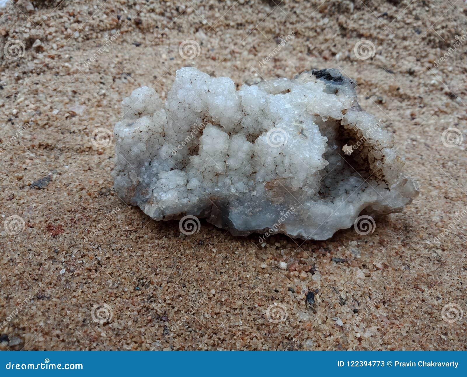 Witte kristalsteen op het zand met textuur geweven behang als achtergrond, strand Oceaan
