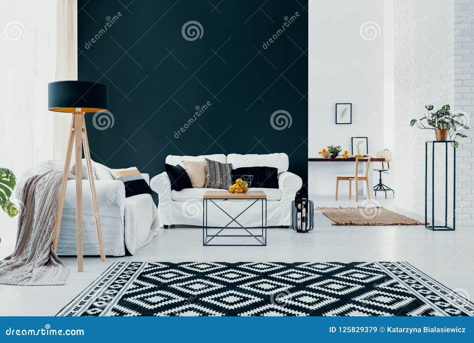 Witte laag tegen zwarte muur in modern woonkamerbinnenland met gevormd tapijt Echte foto