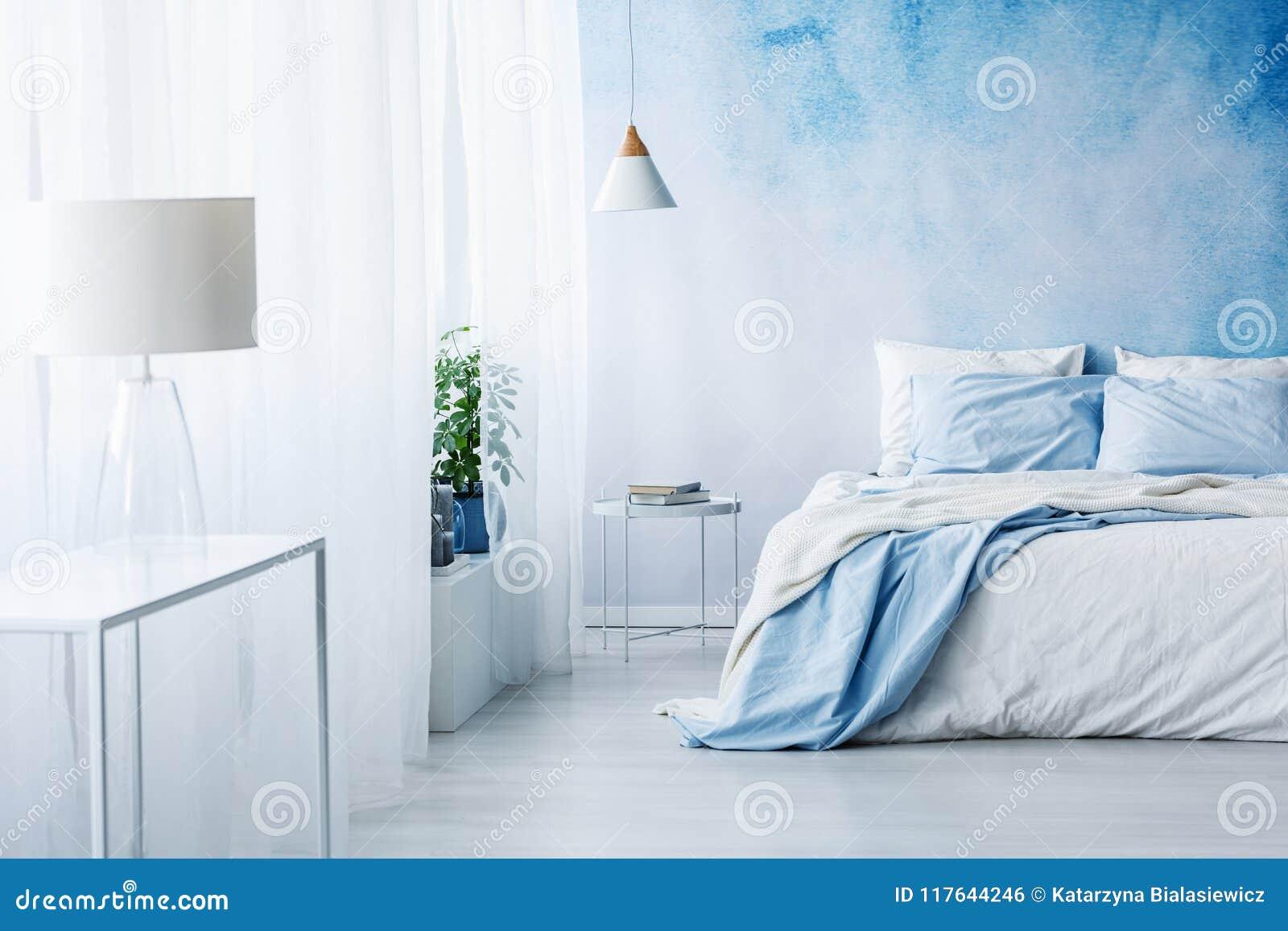 Witte lamp op een lijst in helder blauw slaapkamerbinnenland met bed a