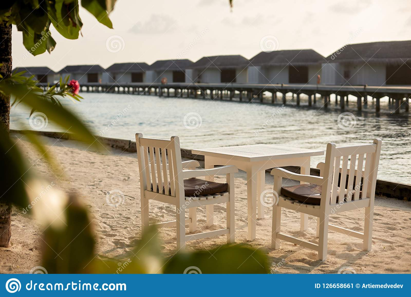 Witte lege lijstlijst en stoelen bij tropische resrraunt op strand in de Maldiven Blauwe oceaanlagune en waterbungalowwen