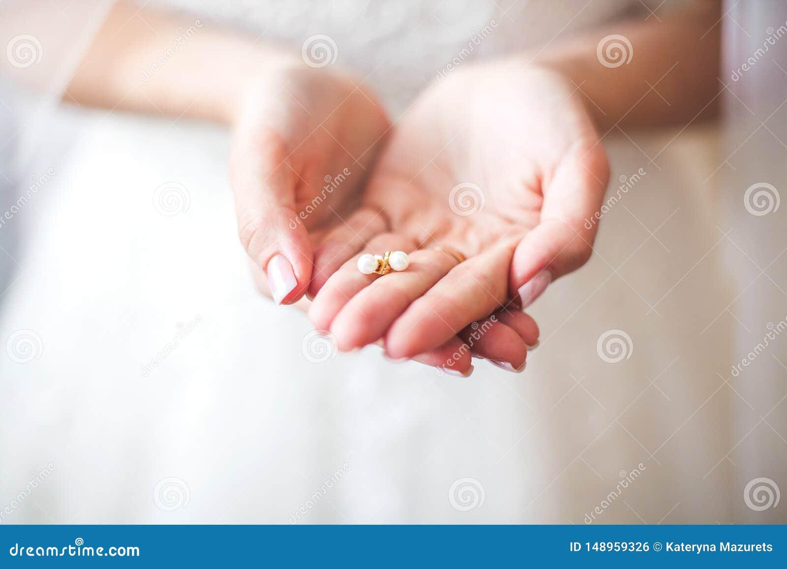 Witte oorringen in handen van de bruid