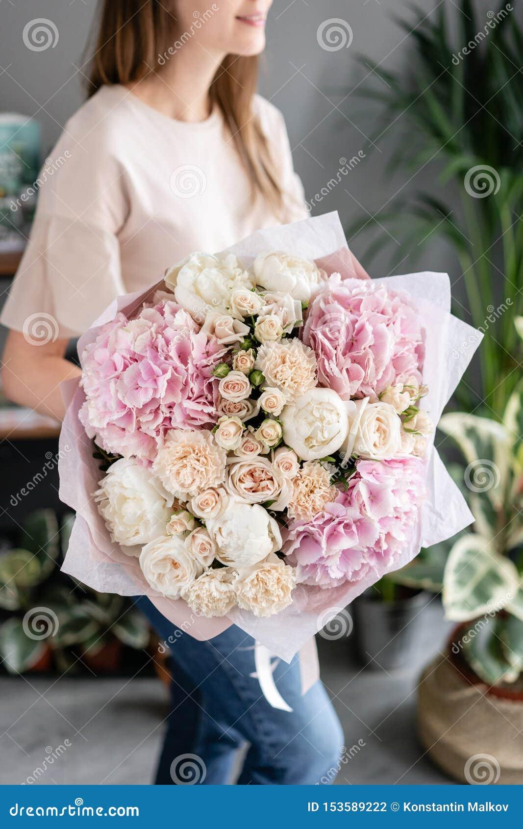 Witte pioenen en roze hydrangea hortensia Mooi boeket van gemengde bloemen in vrouwenhand Bloemenwinkelconcept Knappe vers