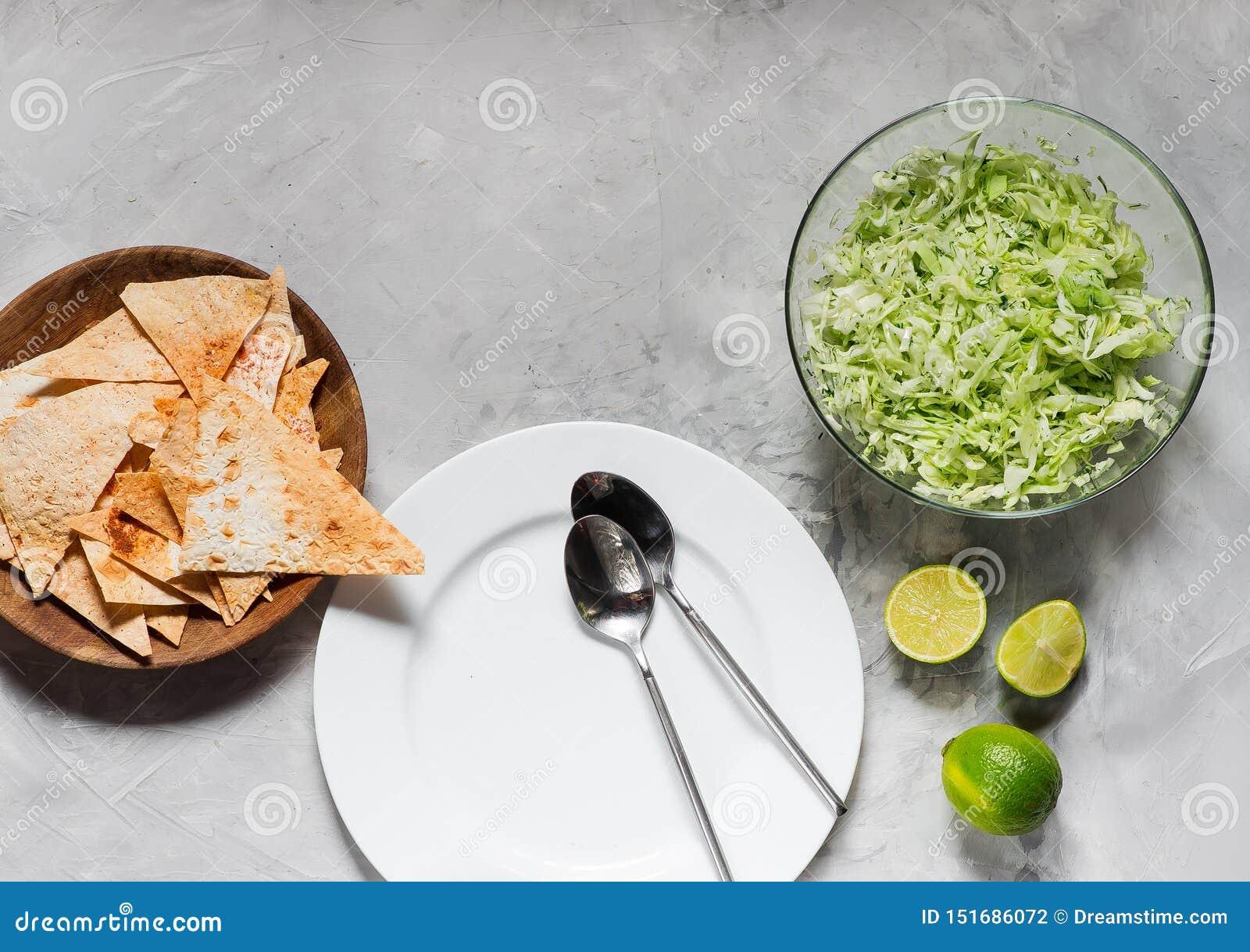 Witte plaat met soeplepels, spaanders en salade van verse kool met greens