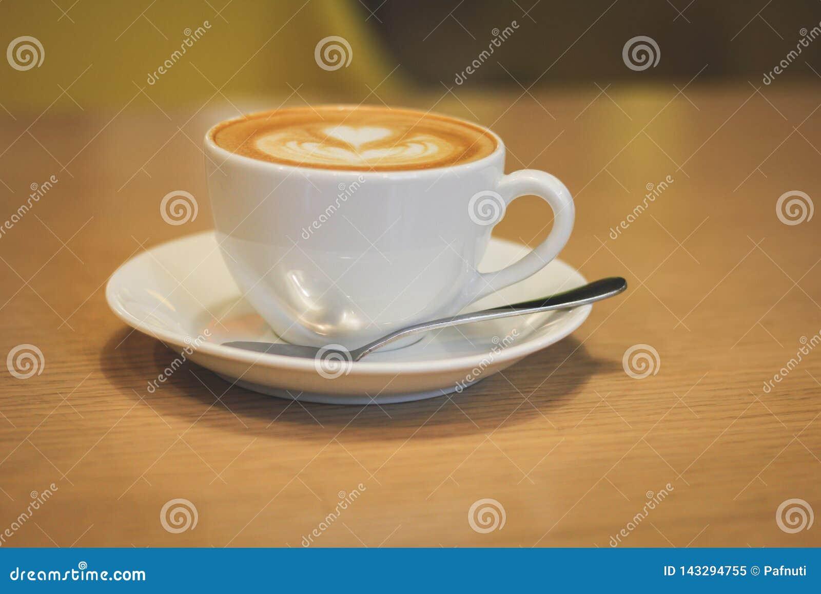 Witte porseleinkop van koffie met een schotel en een lepel