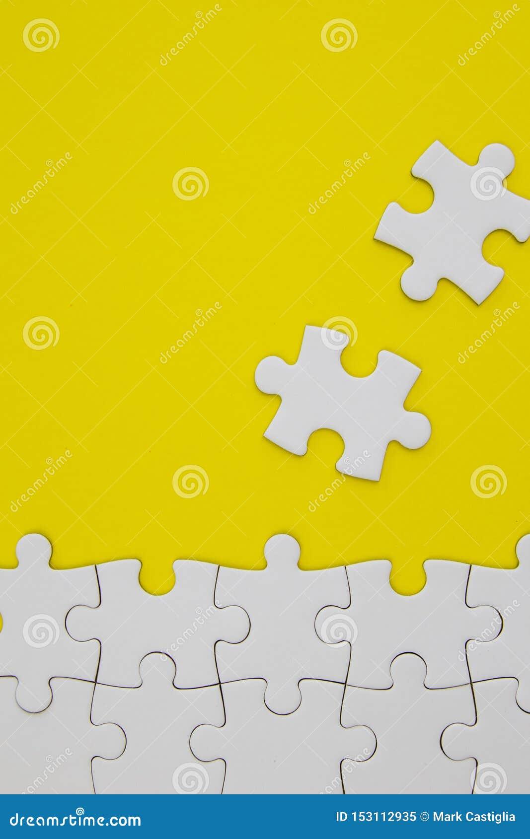 Witte puzzelstukken op gele achtergrond met negatieve ruimte