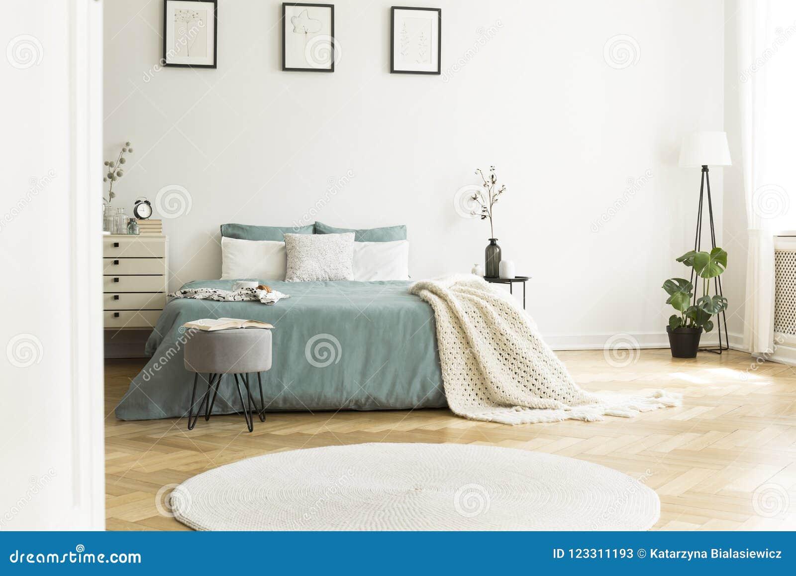 Witte ronde deken voor groen bed met binnen deken in slaapkamer