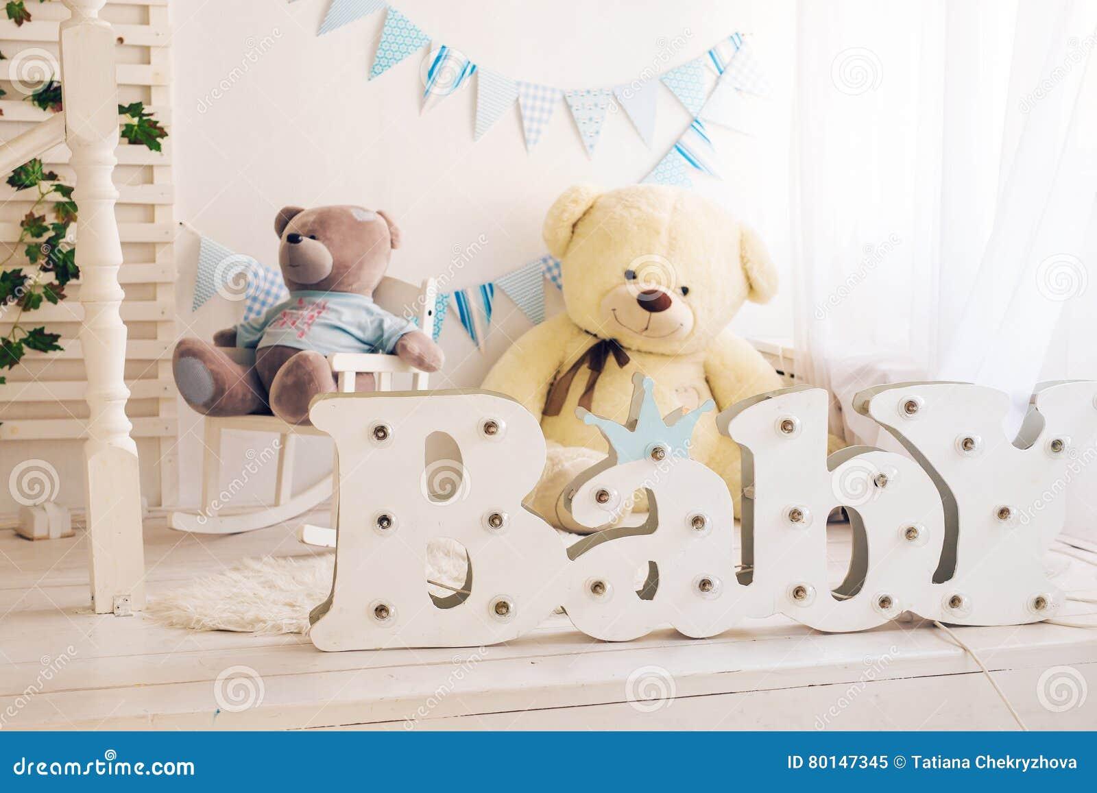 Witte slaapkamer met blauwe ontworpen decoratie en teddybeerideaal