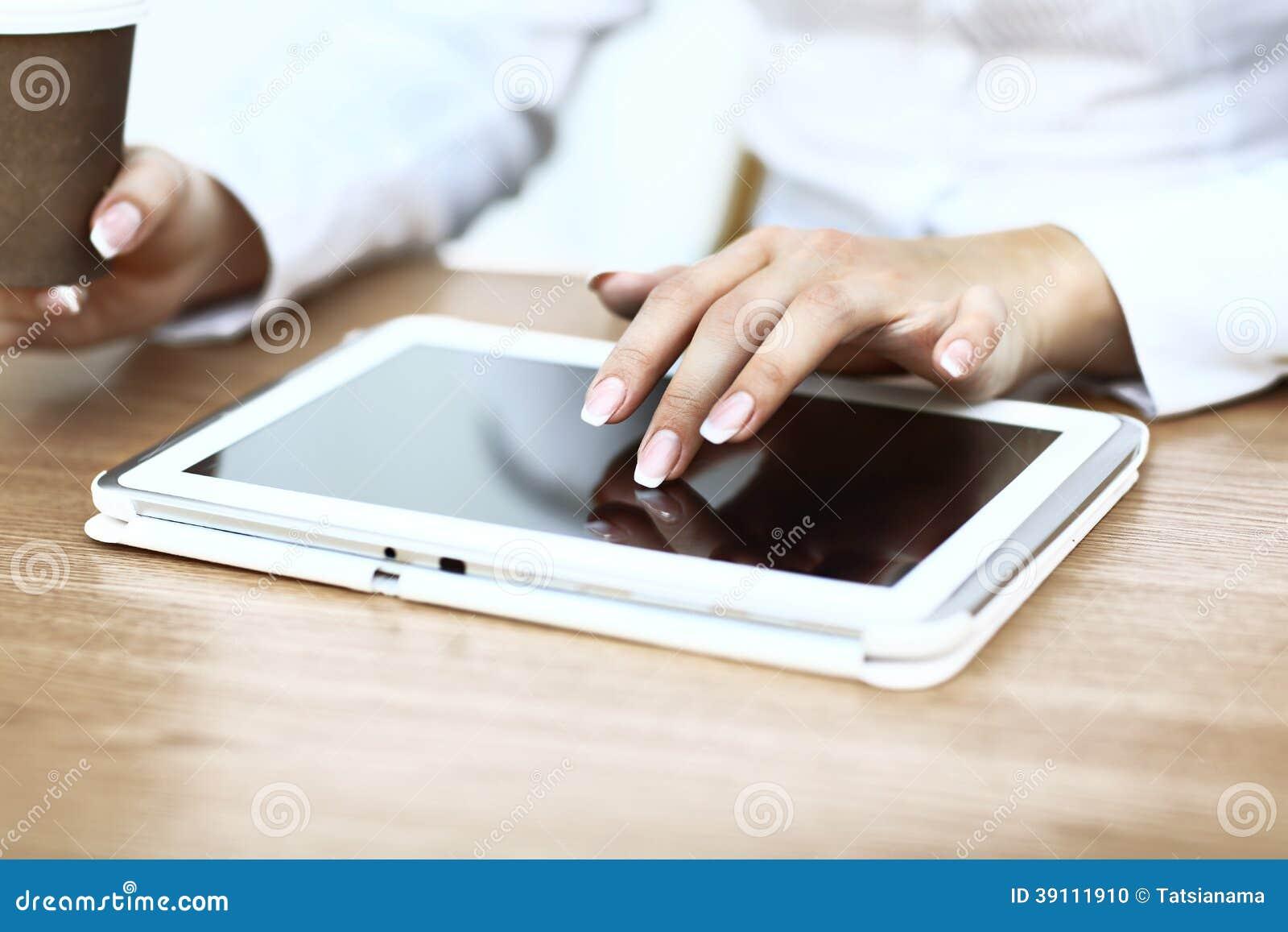 Witte tablet met het leeg scherm in de handen
