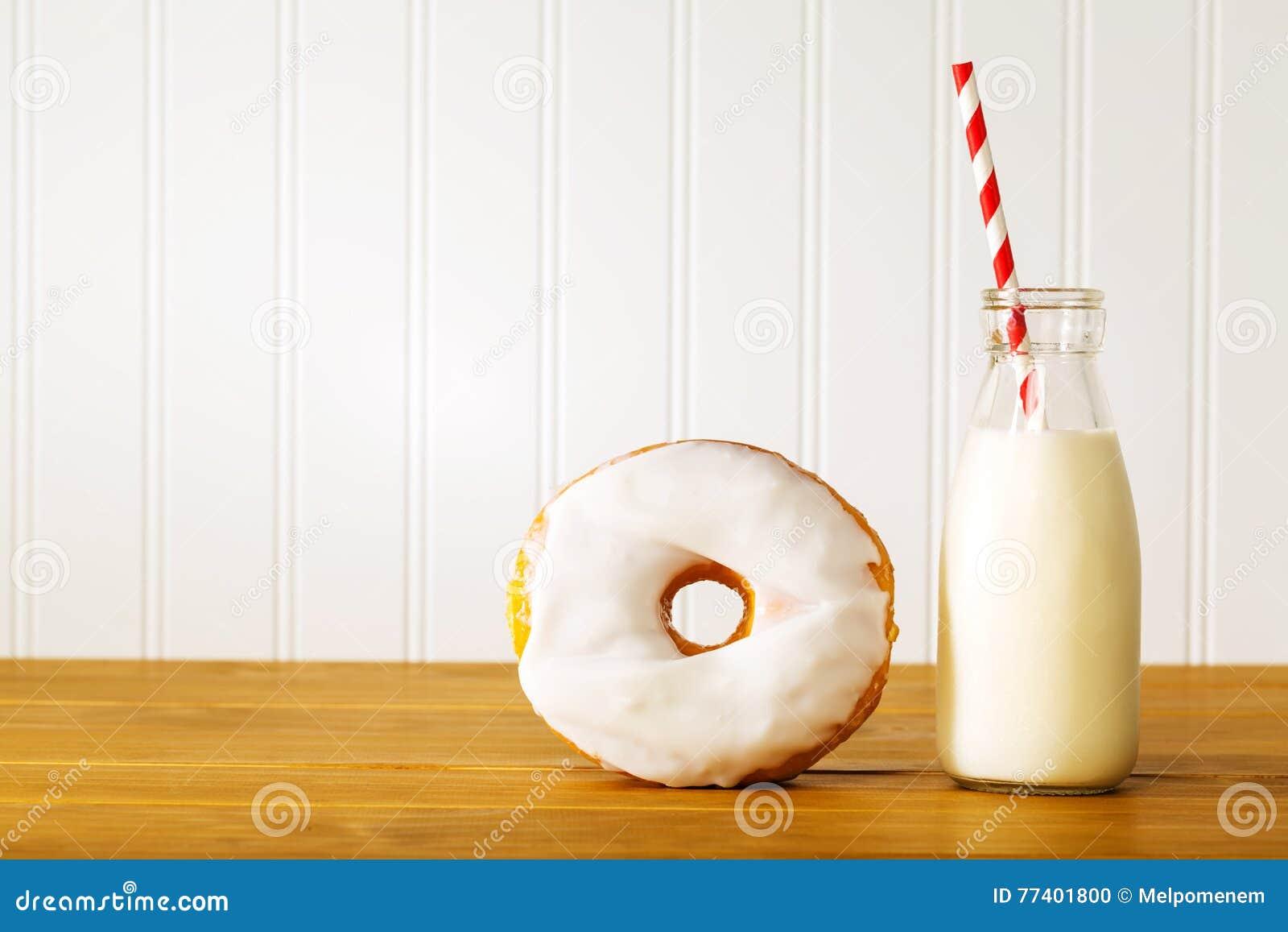 Witte verglaasde doughnut met kruik melk