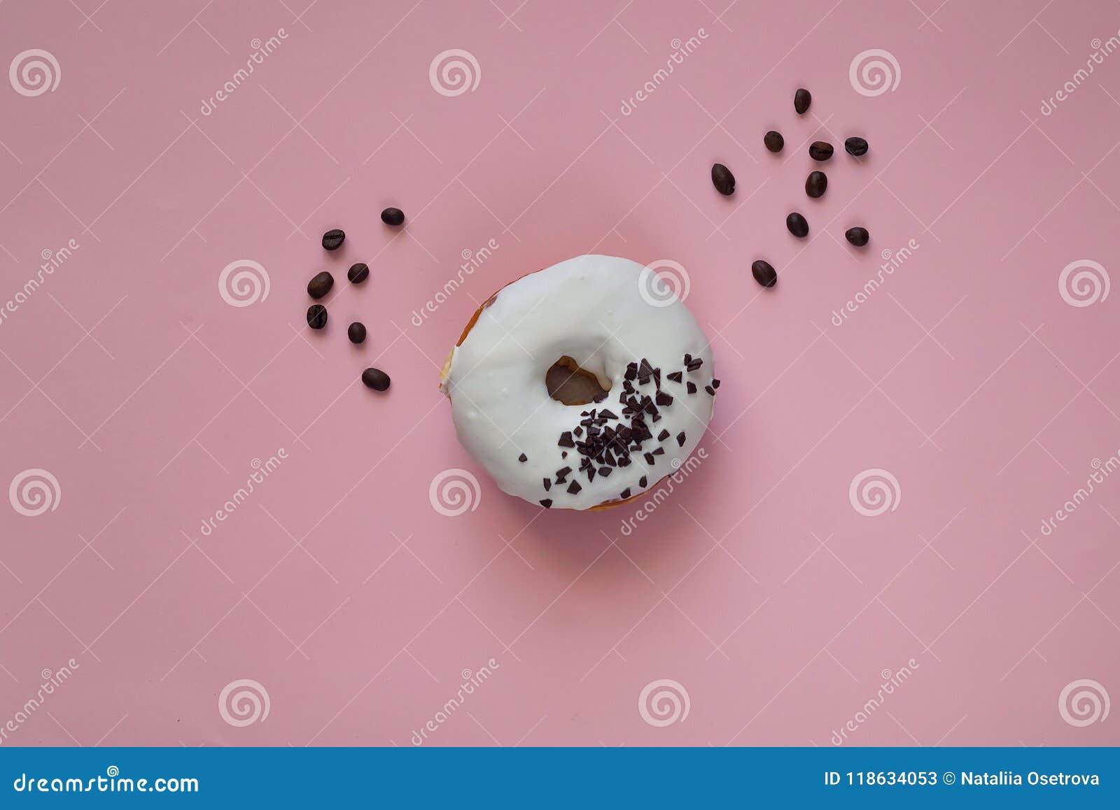 Witte verglaasde doughnut met zwarte chocoladesnoepjes op roze achtergrond Vlak leg Voedselconcept, kleurrijke ontbijtmacro