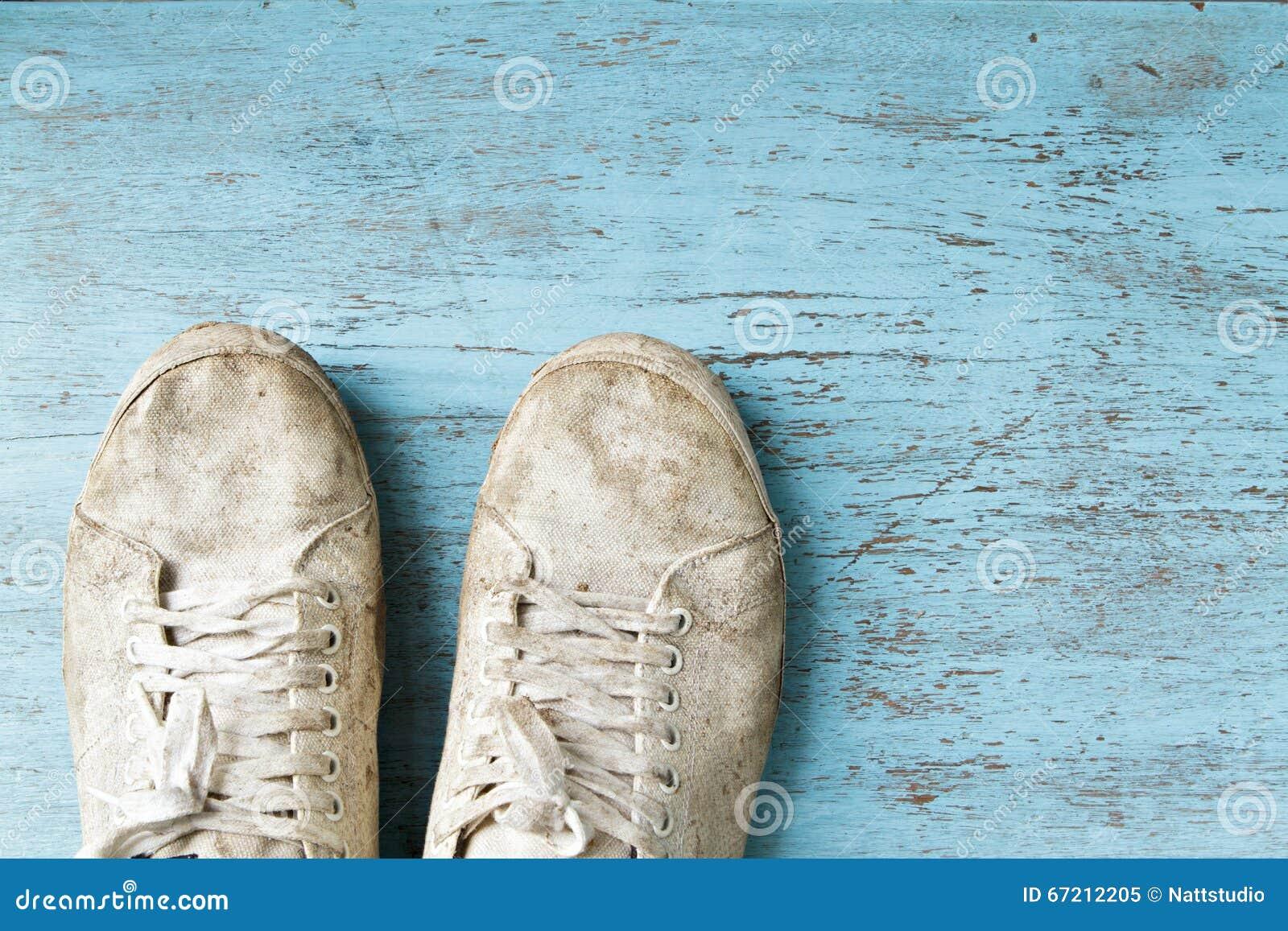 Witte vuile schoen op houten vloer