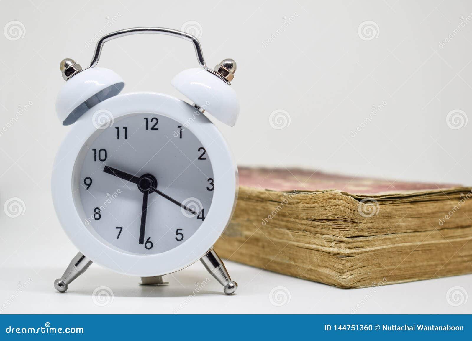 Witte wekker en Oud boek ( Dictionary) op witte achtergrond
