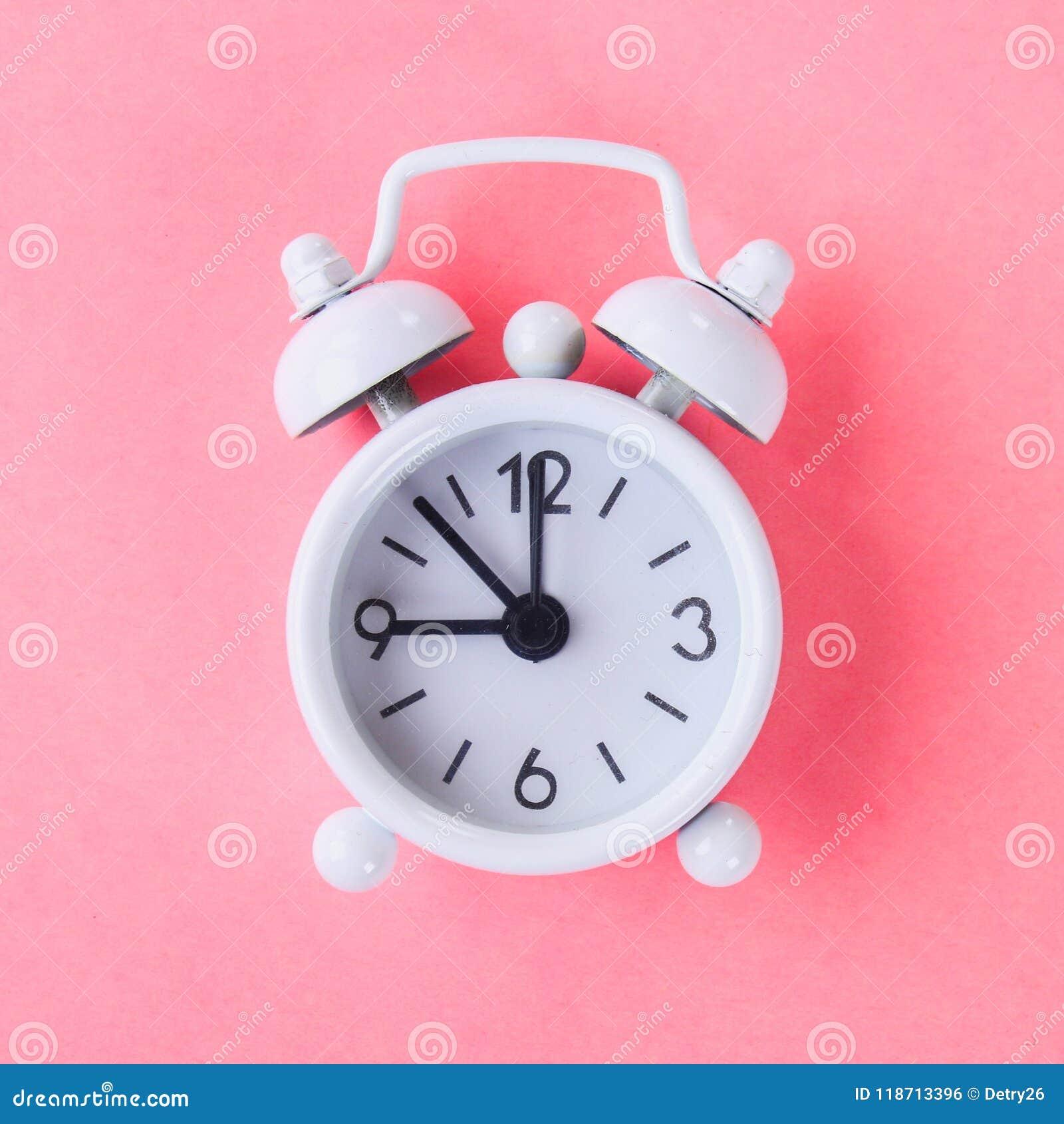Witte wekker op een pastelkleur blauwe, roze achtergrond