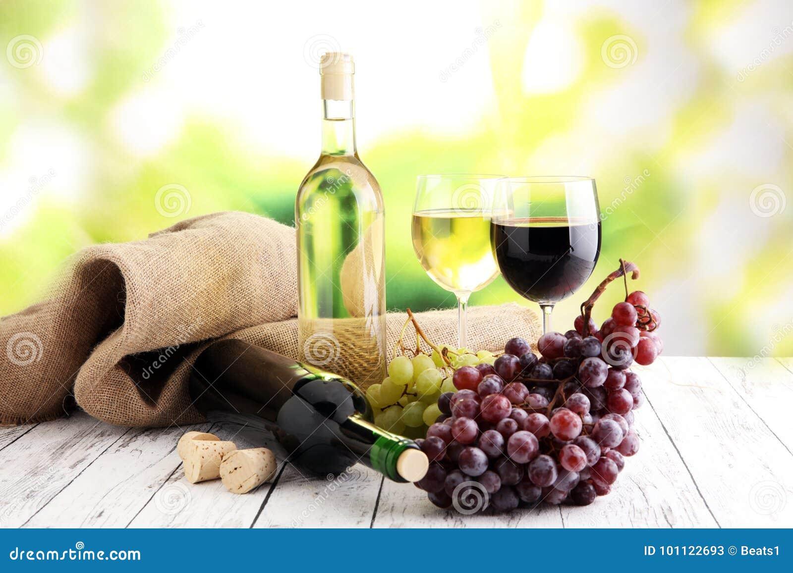 Witte wijn en rode wijn in een glas met dalingsdruiven, witte woode