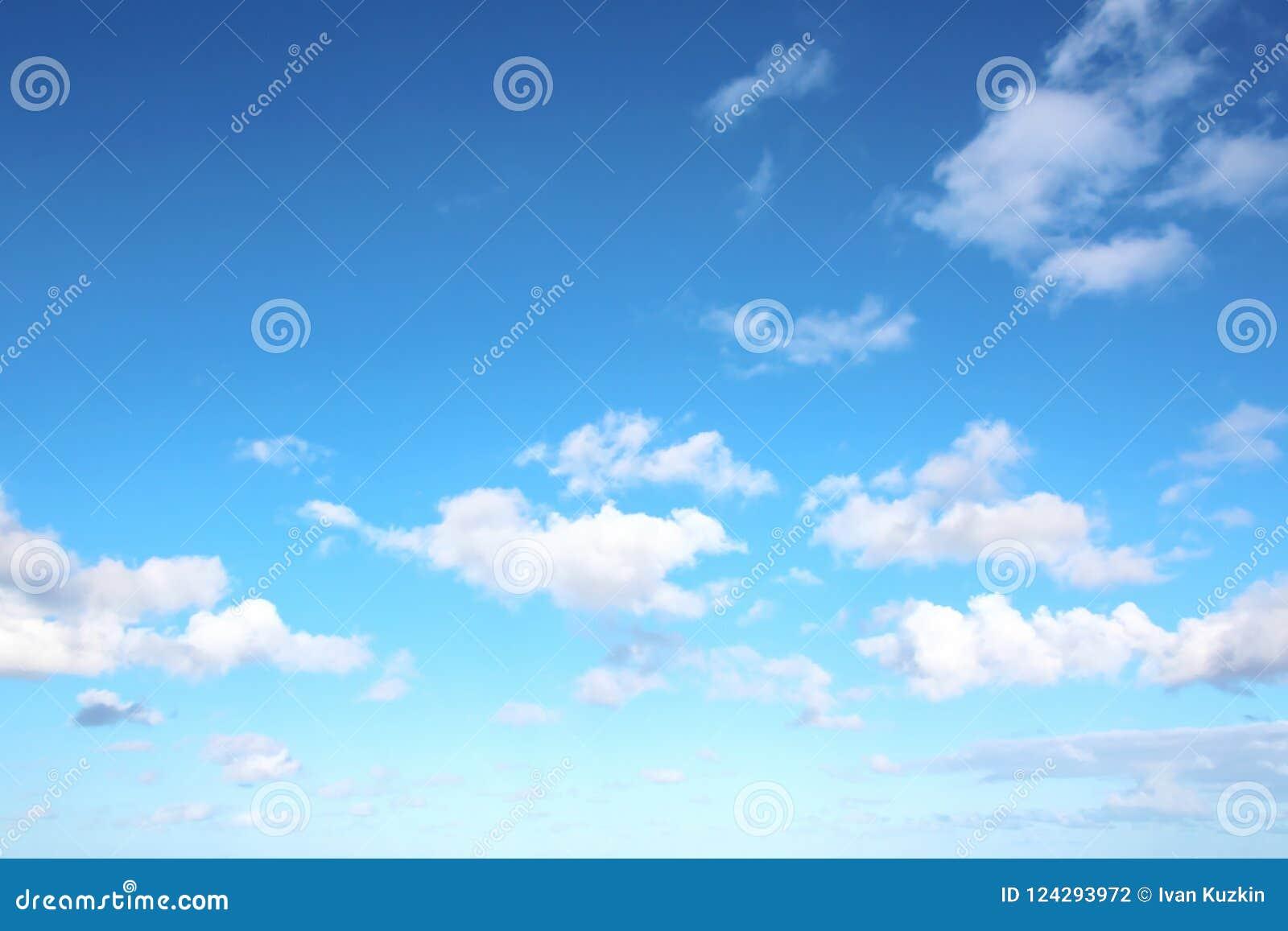 Witte wolken van diverse vormen tegen de blauwe hemel en de zon boven de oppervlakte van de oceaan
