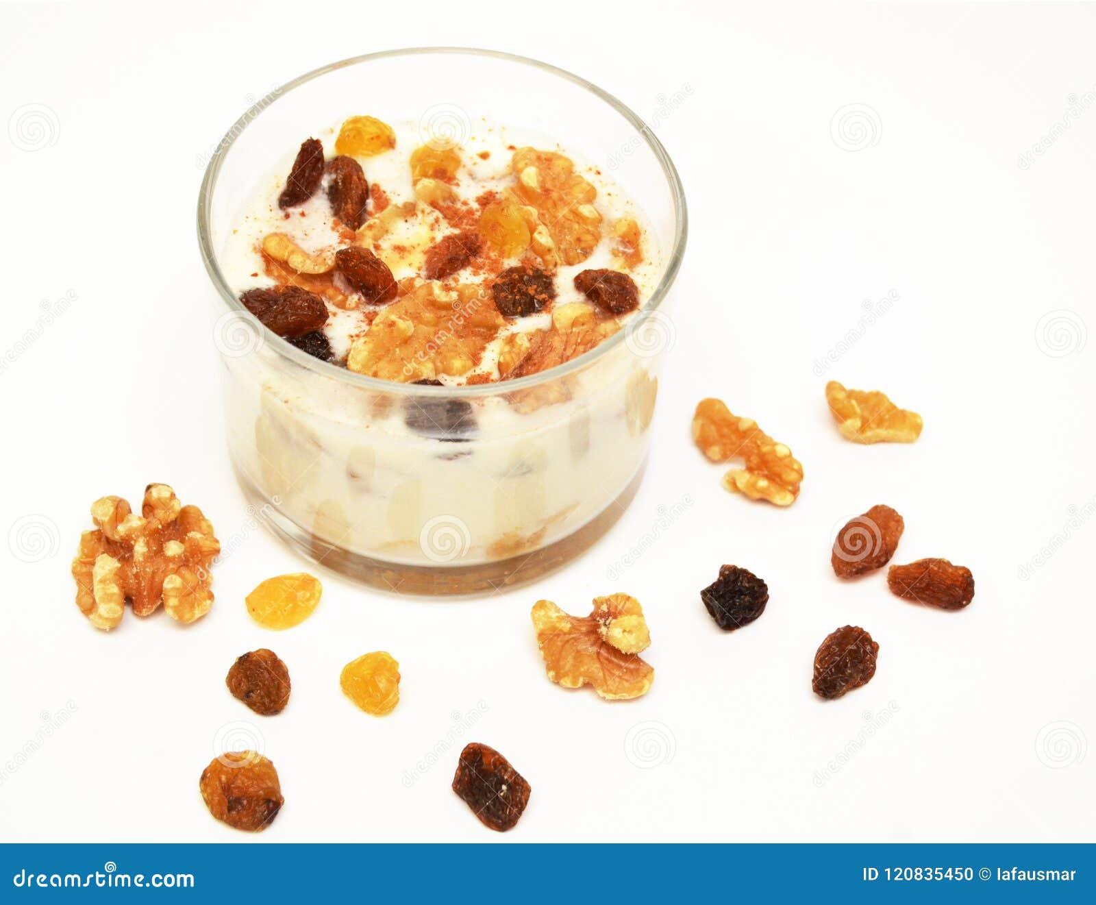 Witte yoghurt met noten en rozijn op witte achtergrond Gezond Ontbijt