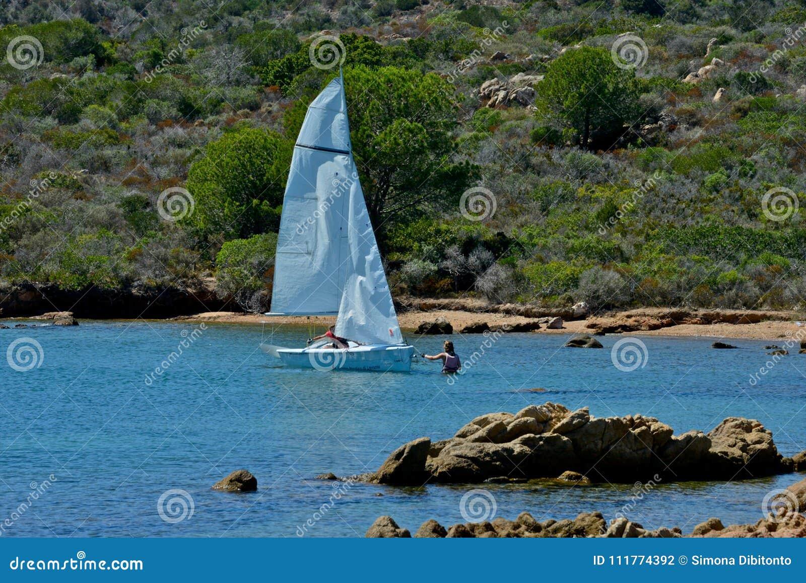 Witte zeilboten met twee mensen die in het blauwe van nature omringde overzees leren te varen
