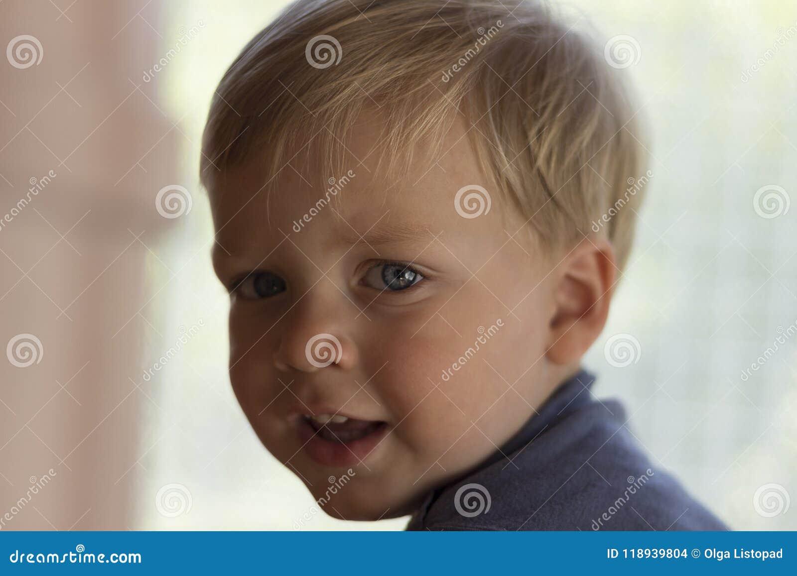Wizerunek śliczna chłopiec, zbliżenia uroczy dziecko na zamazanym tle portret, słodki berbeć z niebieskimi oczami, zdrowymi