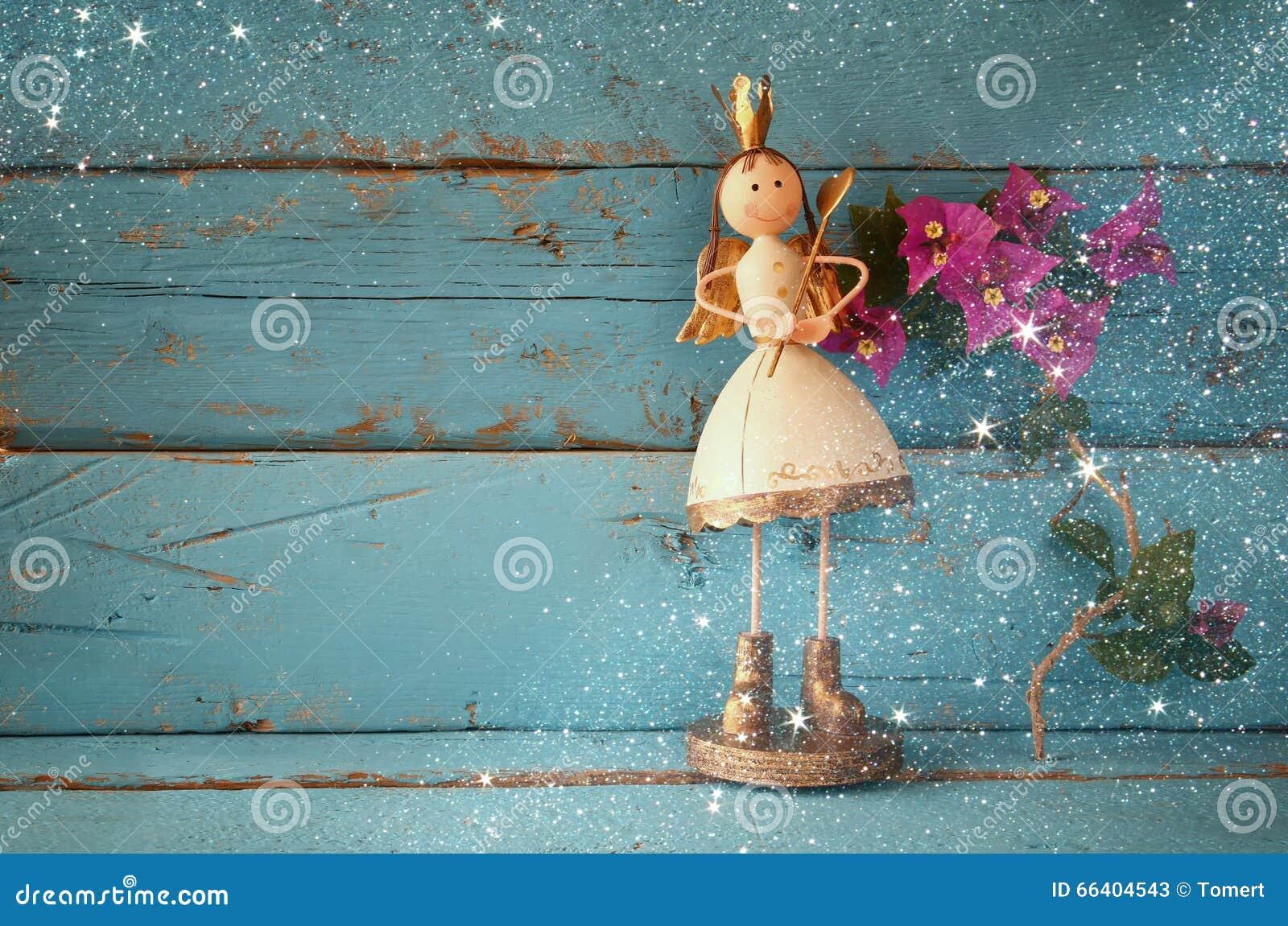 Wizerunek śliczny czarodziejski princess na drewnianym stole rocznik filtrujący z błyskotliwości narzutą
