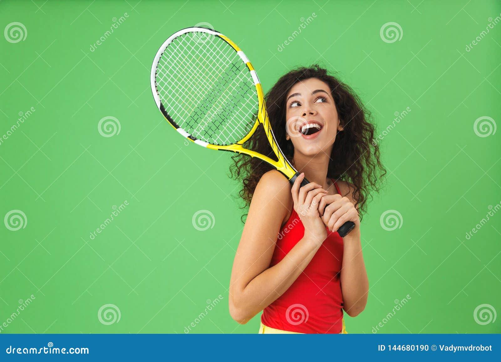 Wizerunek atrakcyjny żeński gracz w tenisa 20s uśmiecha się kant i trzyma