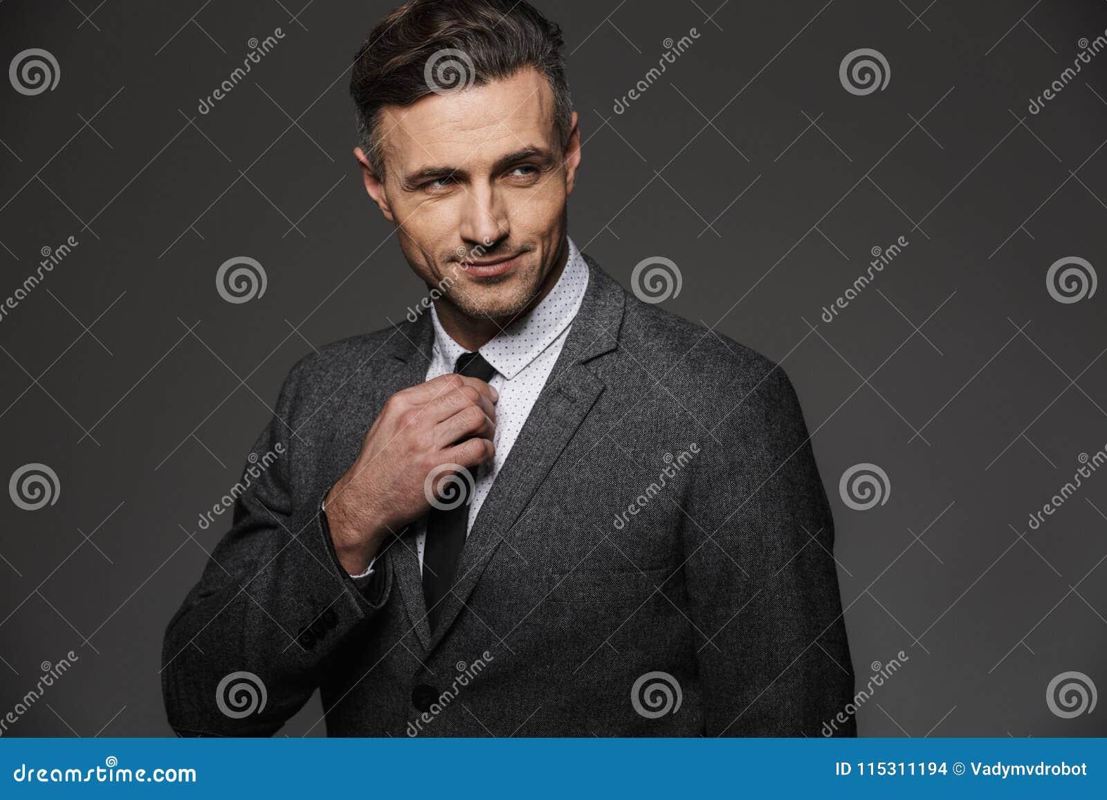 Wizerunek dojrzały zarośnięty mężczyzna jest ubranym garnitur patrzeje na boku