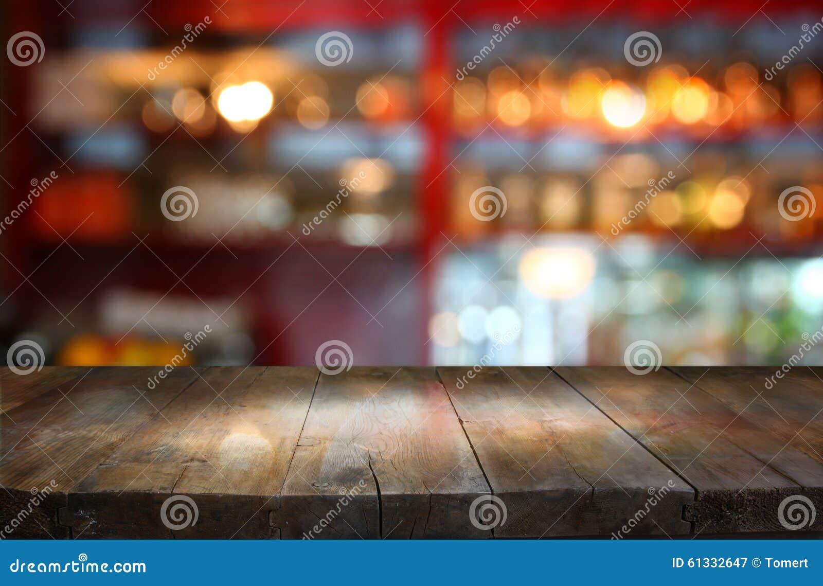 Wizerunek drewniany stół przed abstrakt zamazującym tłem restauracyjni światła