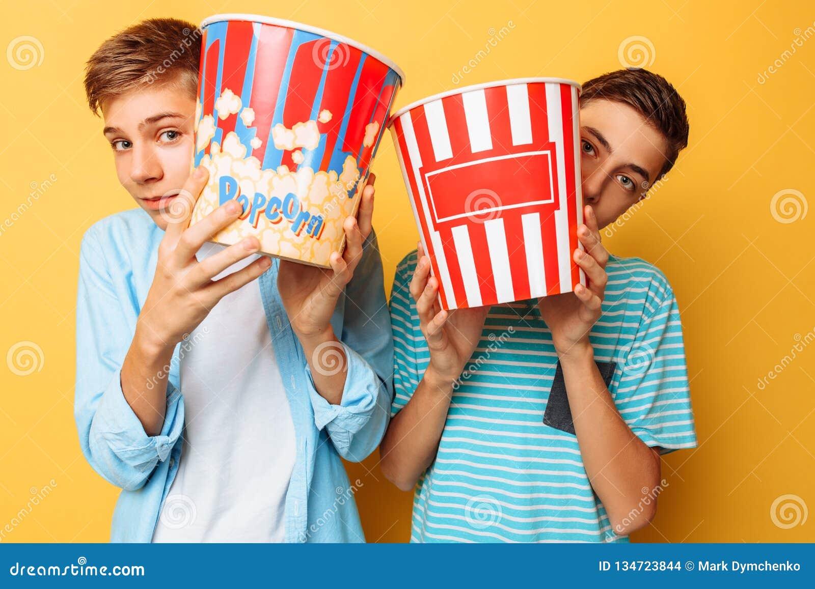 Wizerunek dwa przestraszył nastolatków, faceci ogląda horror i chuje za wiadrem popkorn na żółtym tle