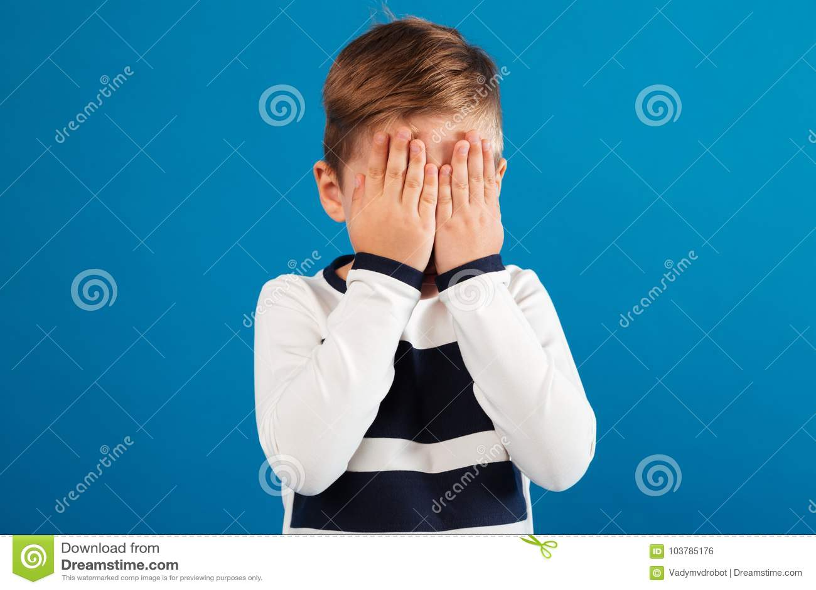 Wizerunek Młoda chłopiec w pulowerze zakrywa jego twarz