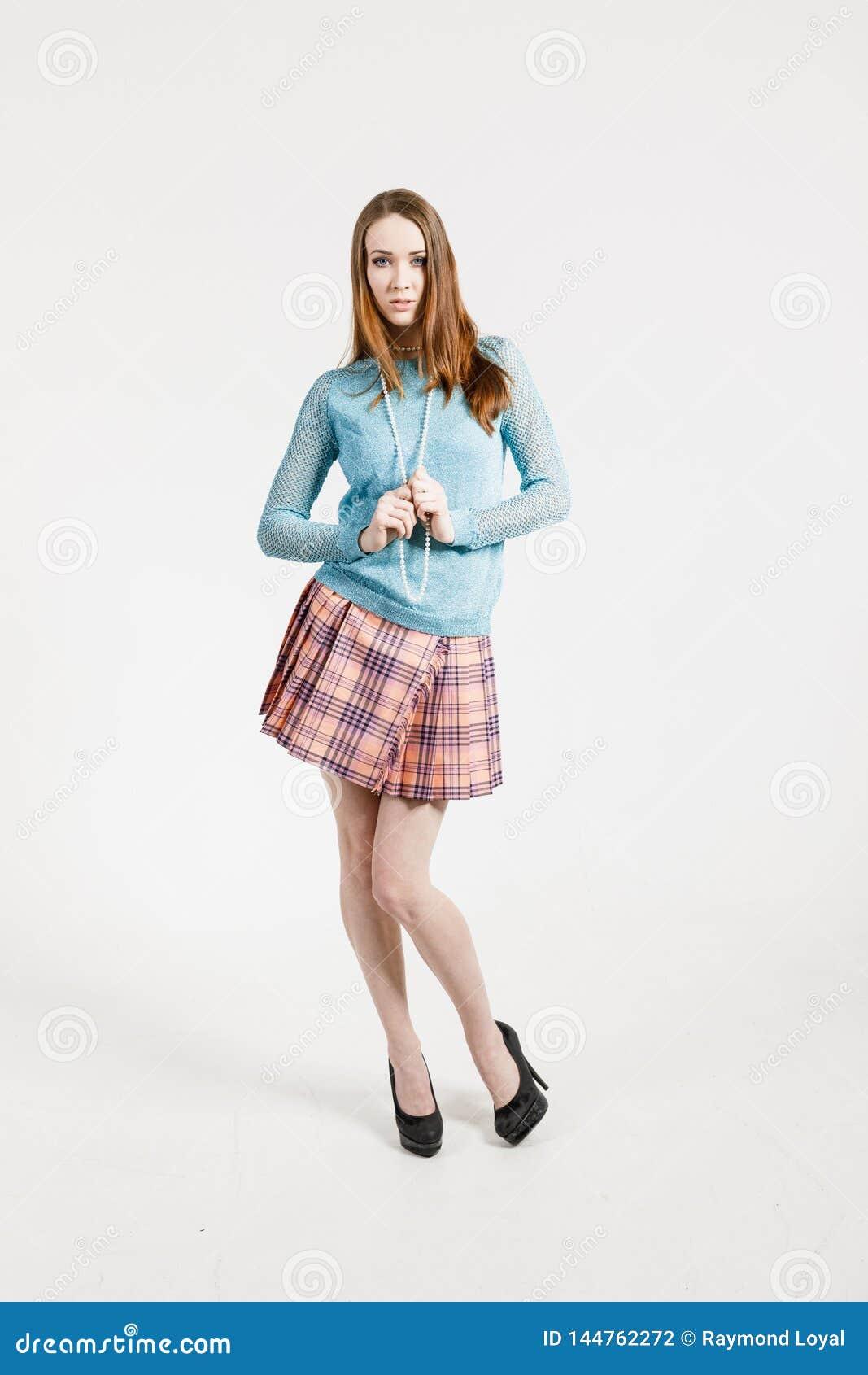 Wizerunek młoda kobieta jest ubranym krótką spódnicę i turkusowego pulower