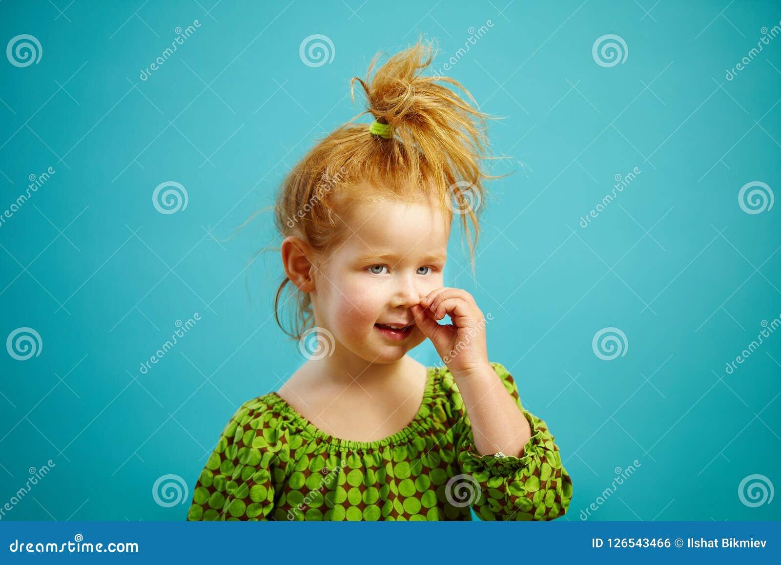 Wizerunek mała miedzianowłosa śmieszna dziewczyna podnosi jego nos odizolowywającego na błękitnym tle Jaskrawy portret śliczny dz