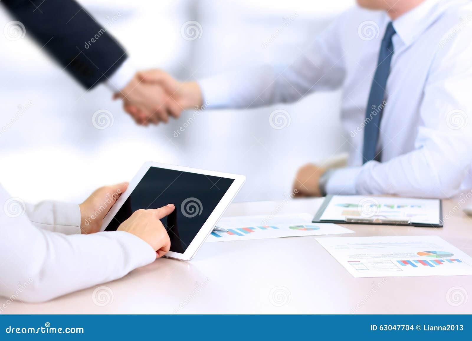 Wizerunek partnera biznesowego handshaking nad biznesem protestuje na miejscu pracy Z cyfrową pastylką bizneswomanu działanie