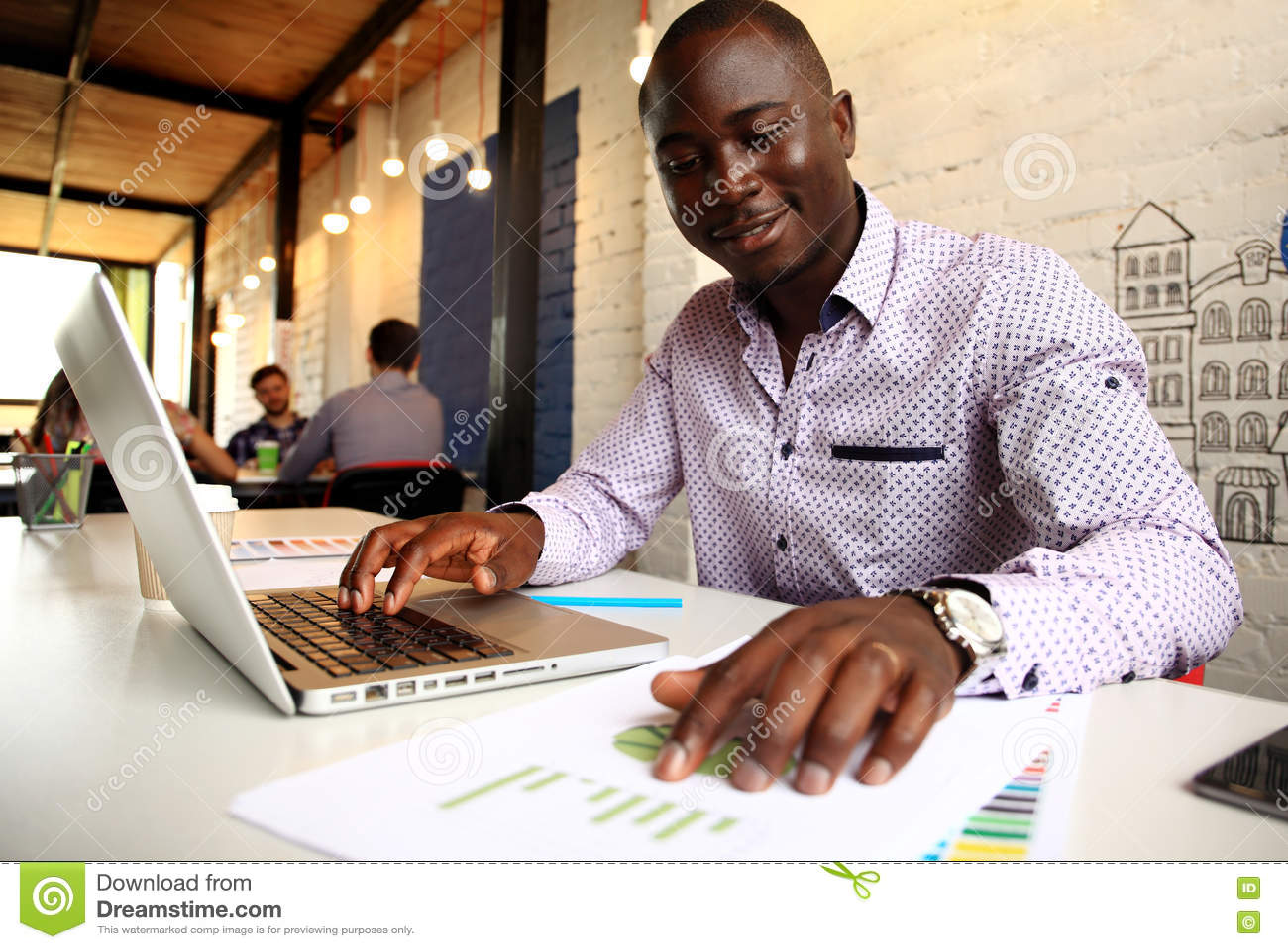 Wizerunek pracuje na jego laptopie amerykanina afrykańskiego pochodzenia biznesmen Przystojny młody człowiek przy jego biurkiem