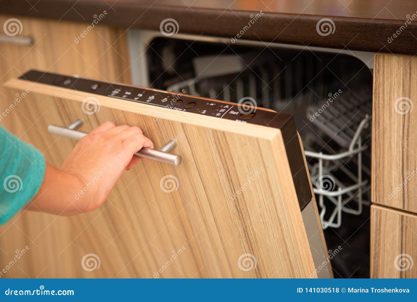 Wizerunek ręka mężczyzny otwarcia zmywarki do naczyń