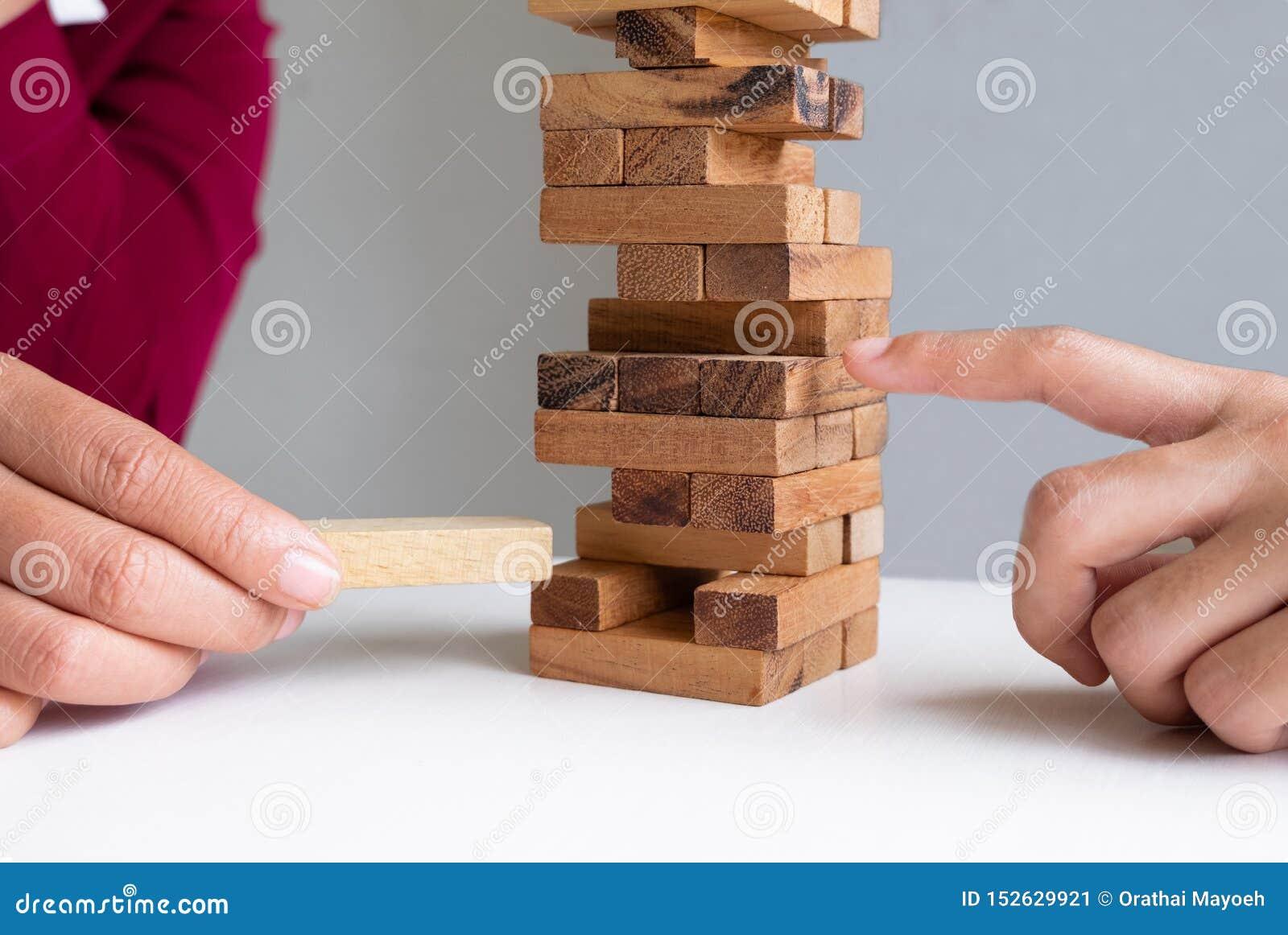 Wizerunek ręki mienie blokuje drewnianą grę narastającą w górę biznesu Ryzyko zarządzania i strategii plan