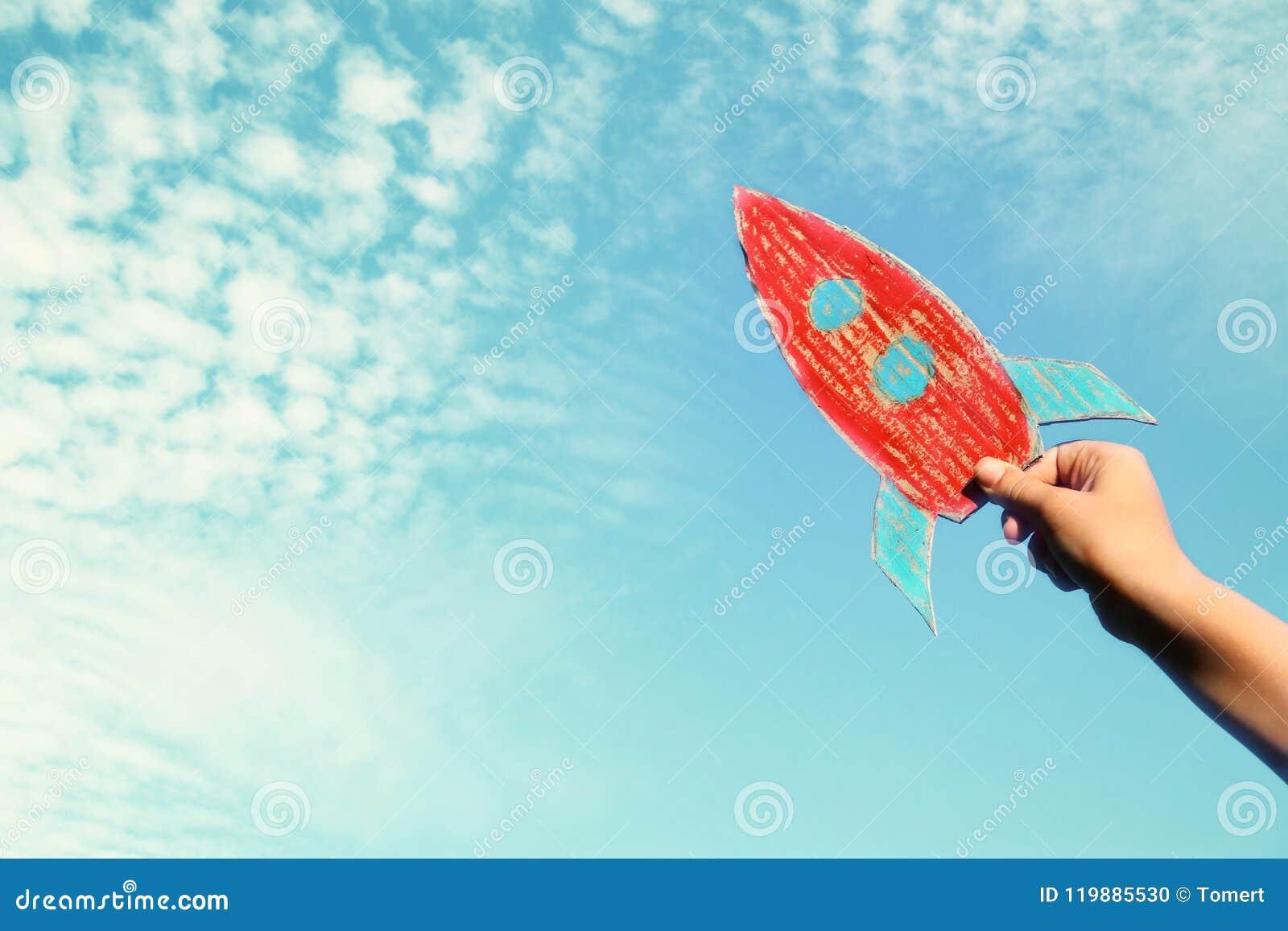 Wizerunek trzyma rakietę przeciw niebu męska ręka wyobraźnia i sukcesu pojęcie