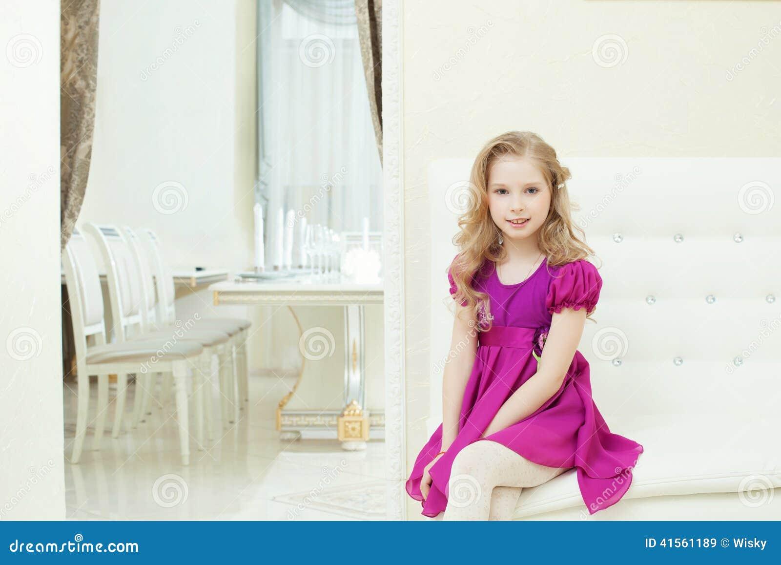 Wizerunek uśmiechnięta śliczna dziewczyna w mądrze purpurach ubiera