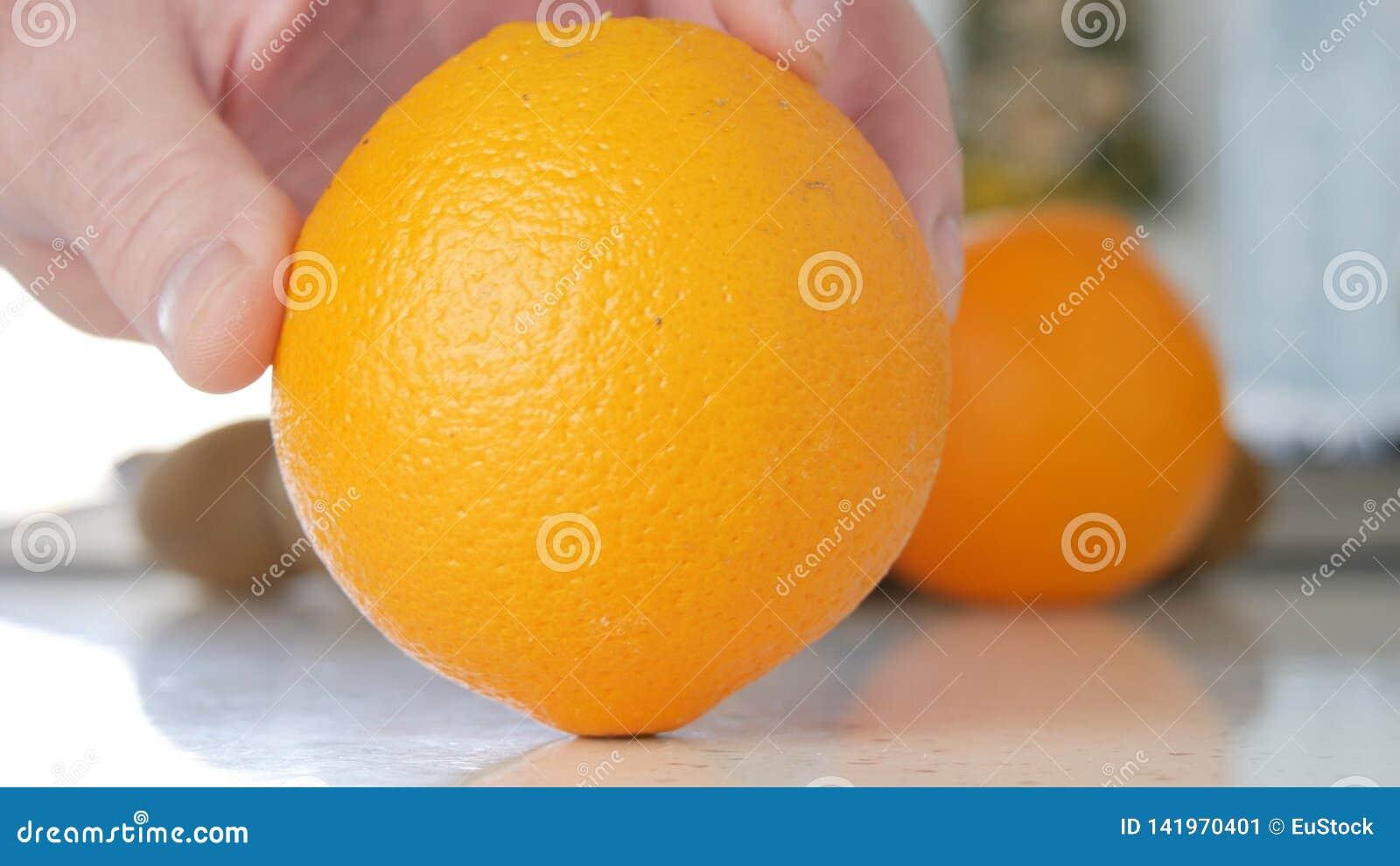 Wizerunek z mężczyzna ręką na kuchni Przedstawia Piękną Pomarańczową owoc