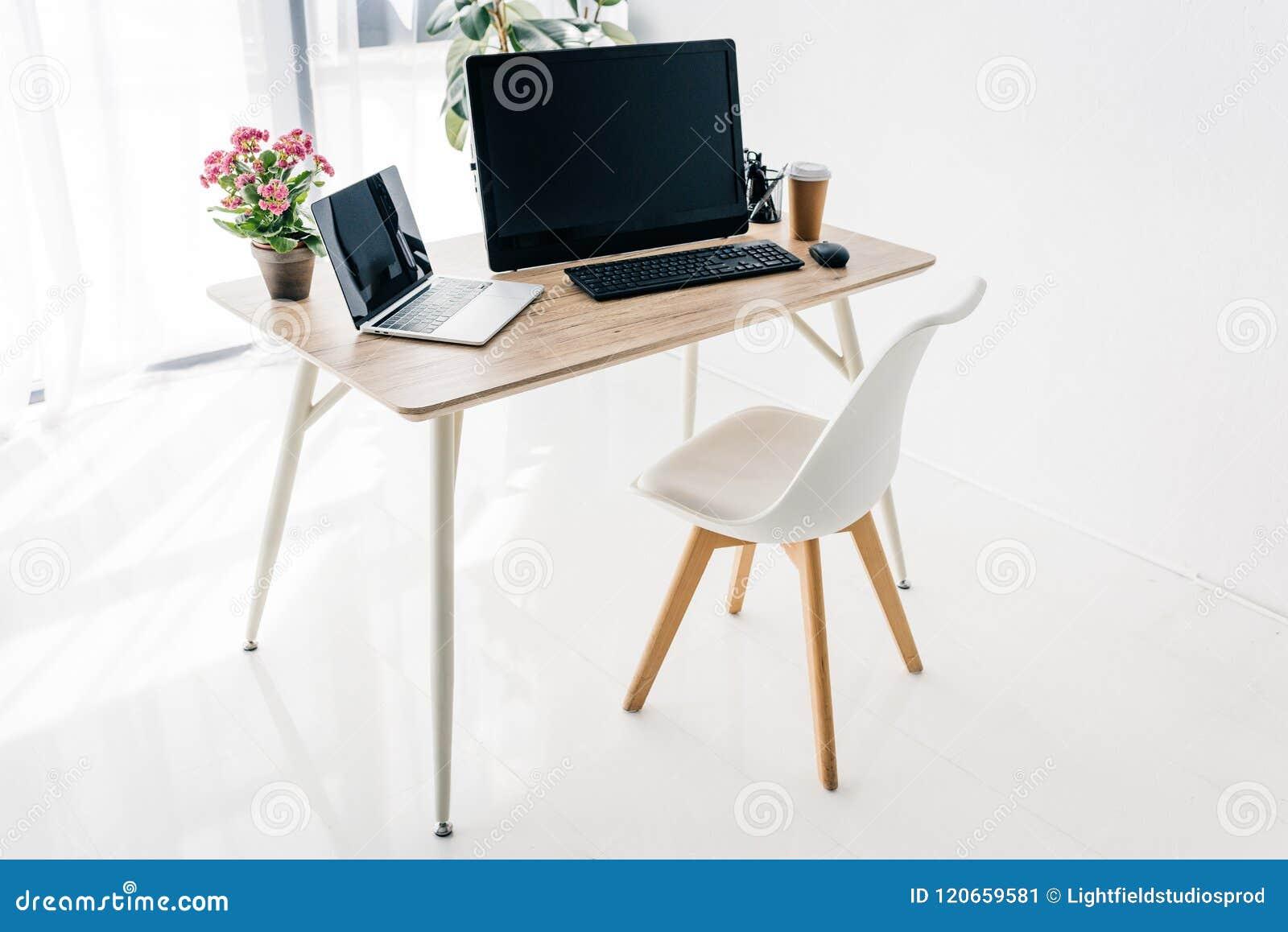 Wnętrze miejsce pracy z krzesłem, kwiatami, kawą, materiały, laptopem i komputerem,