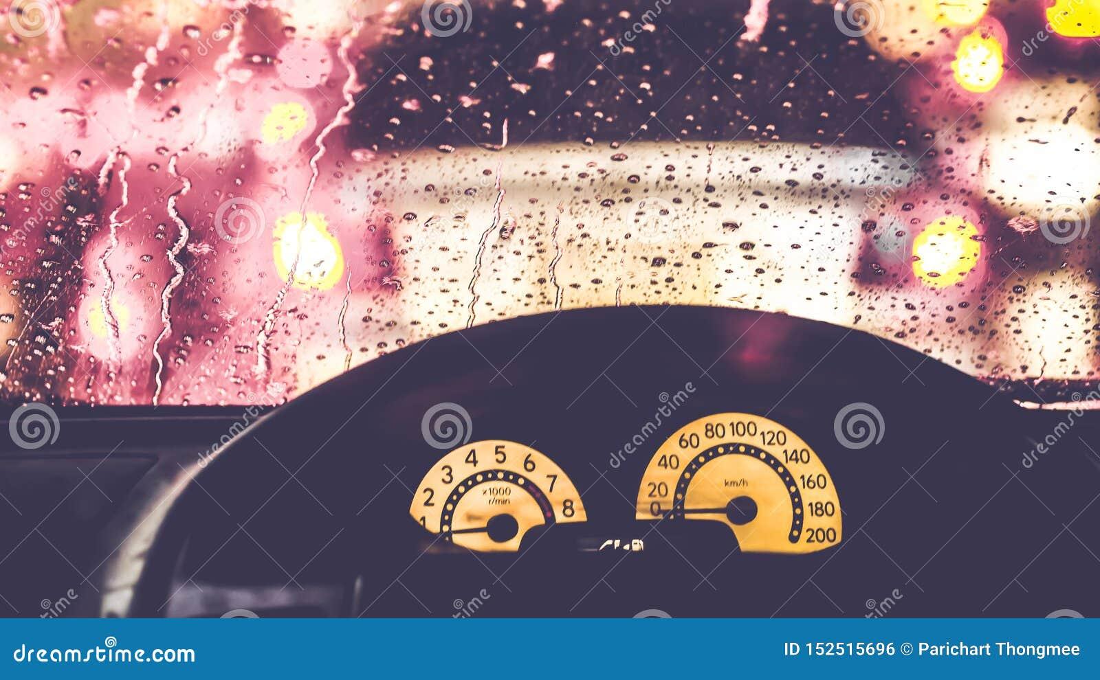 Wnętrze samochód gdy deszcz plama światło na drodze w pada dniu