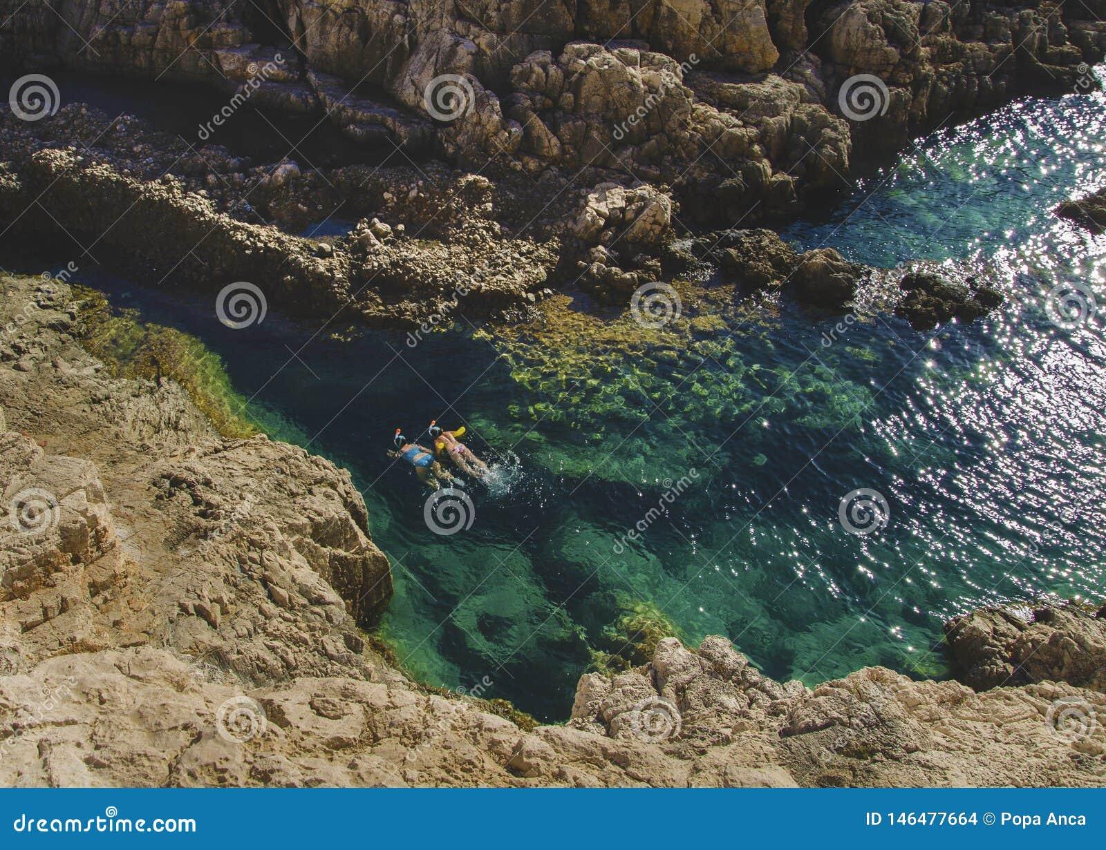 Wo-personer som simmar och snorklar i det kristallklara turkosvattnet i Korakonissi, Zakynthos