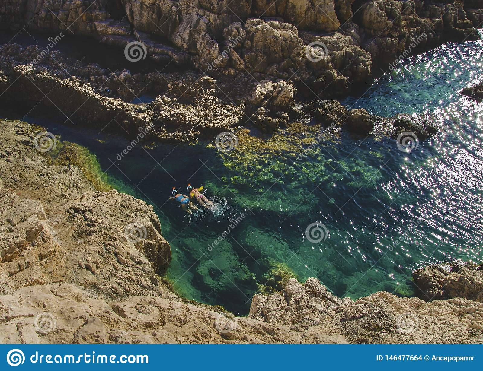 Wo persons swimming and snorkeling in the crystal clear turquoise water in Korakonissi, Zakynthos