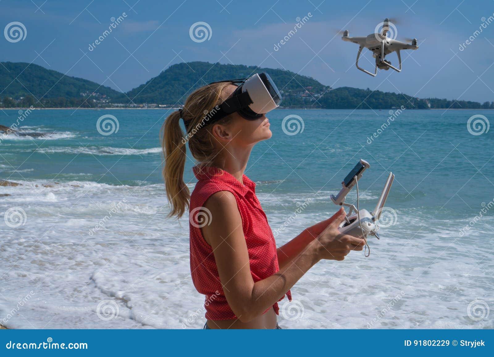 Woan при стекла камеры и виртуальной реальности трутня принимая фото и видео на пляже