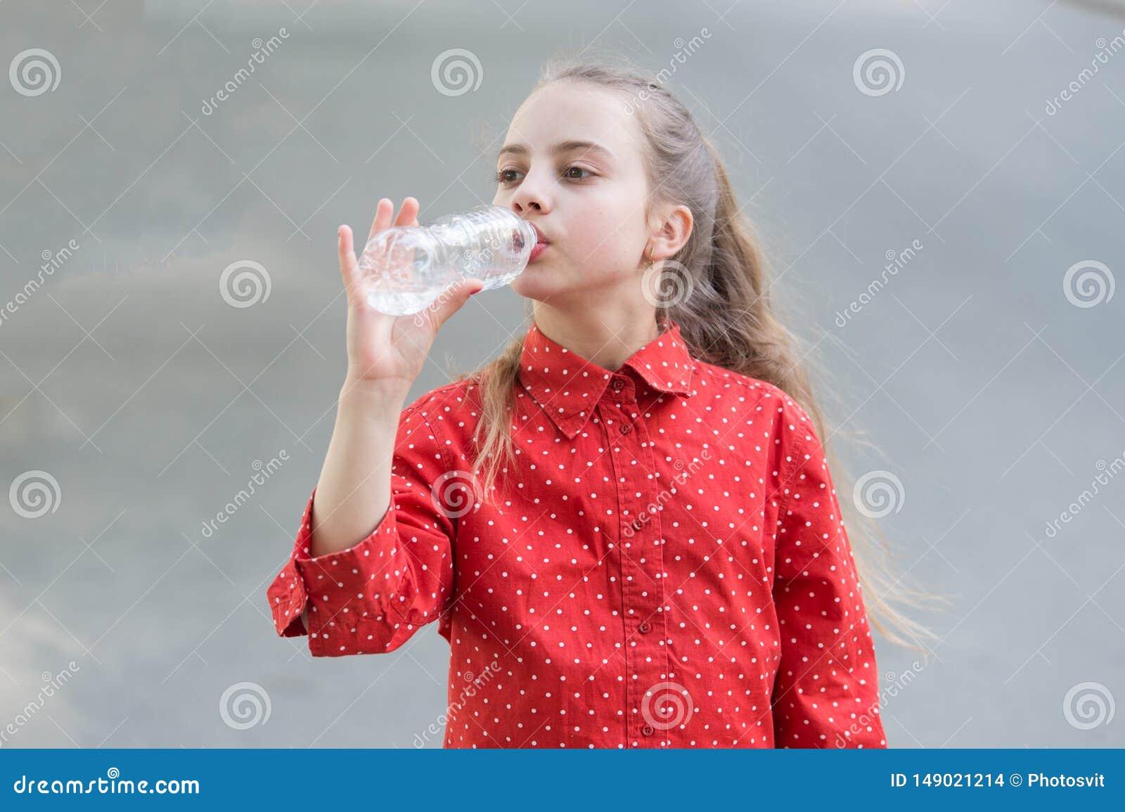 Woda jest ?yciem Spragniony dziecko pije świeżą wodę od plastikowej butelki Mała dziewczynka ma napój od bidonu
