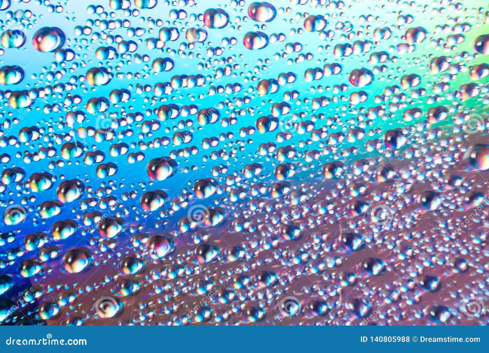 Woda opuszcza na dvd środkach, wod krople na kolorowym tle