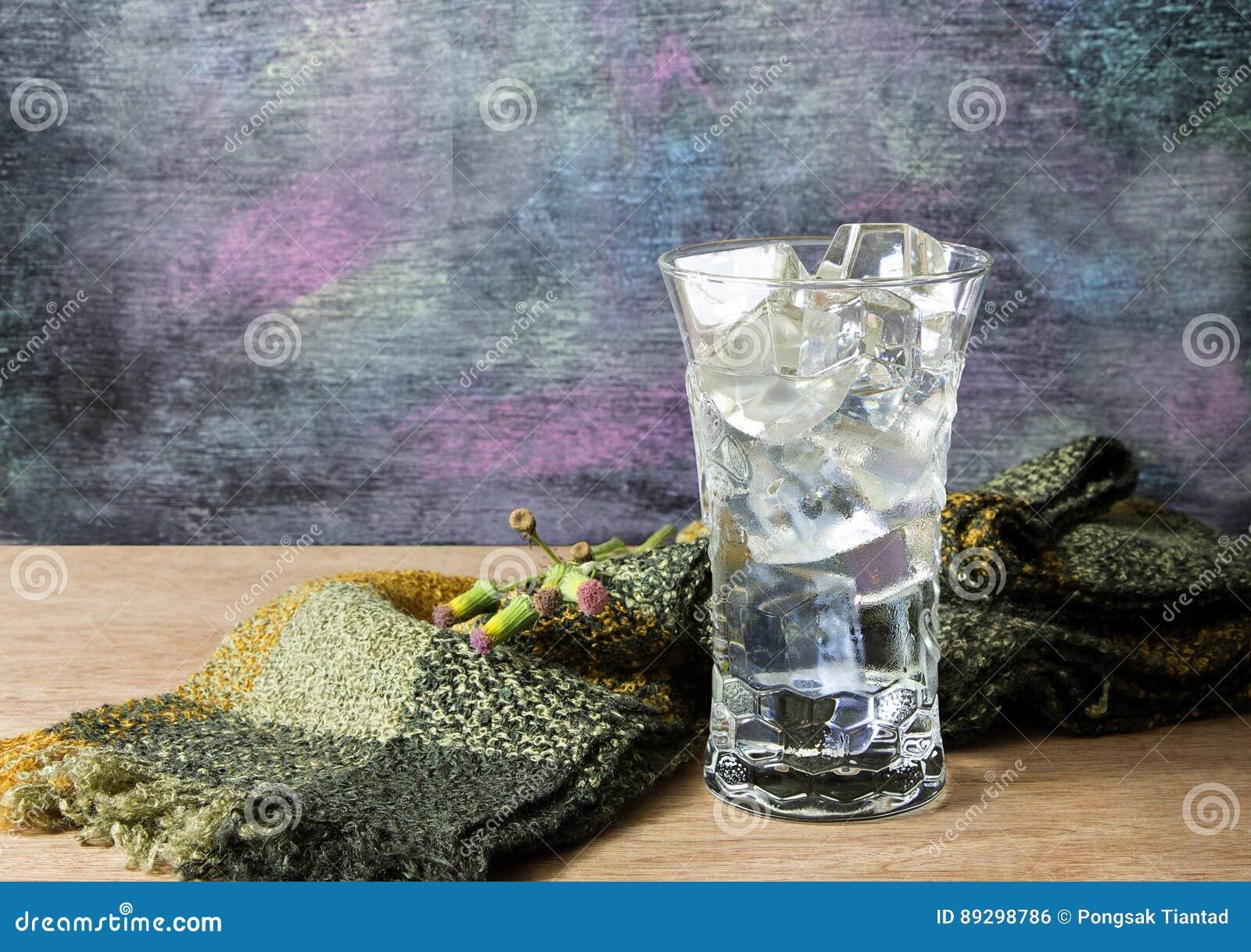 Woda w szkle z lodem umieszczającym na drewnianym stole i blackboard