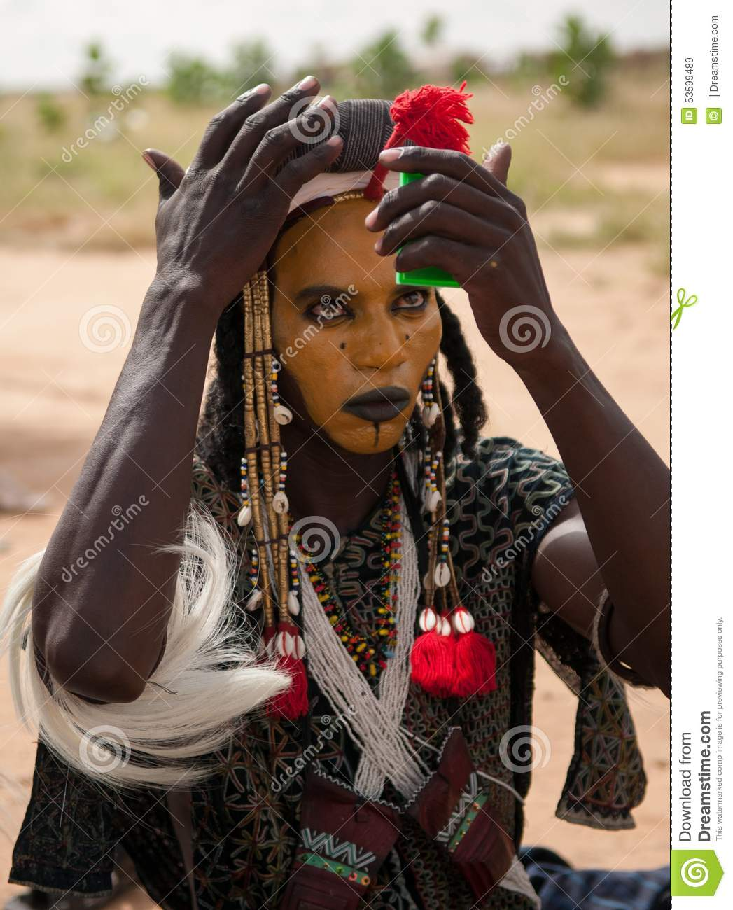 wodaabe man checking makeup in a mirror gerewol niger
