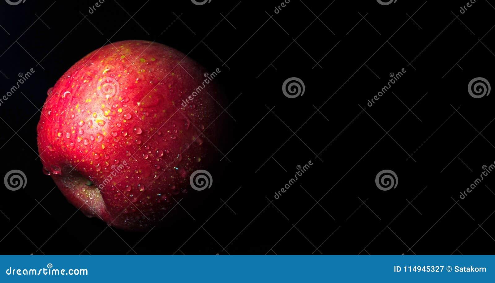 Wodna kropelka na glansowanej powierzchni czerwony jabłko na czarnym tle